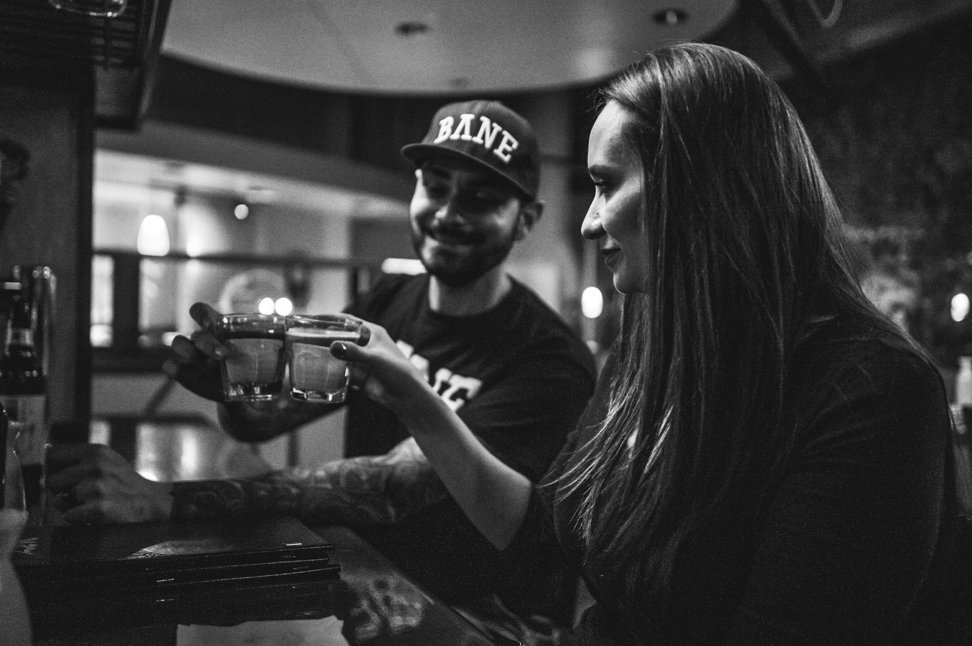A couple in a restaurant cheers as they prepare to take saki bombs, black & white, Denver, Colorado