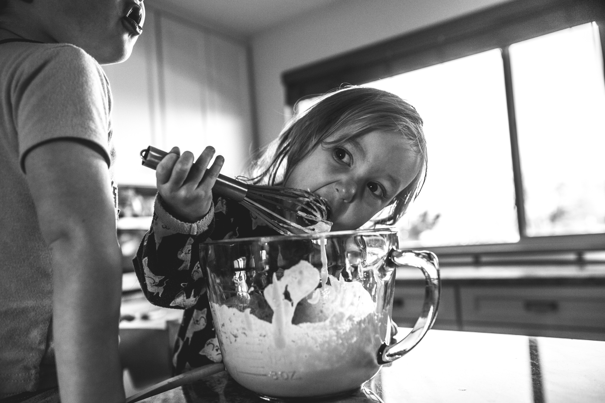 Little girl eating pancake batter off of a whisk out of the bowl, black and white, Denver, Colorado