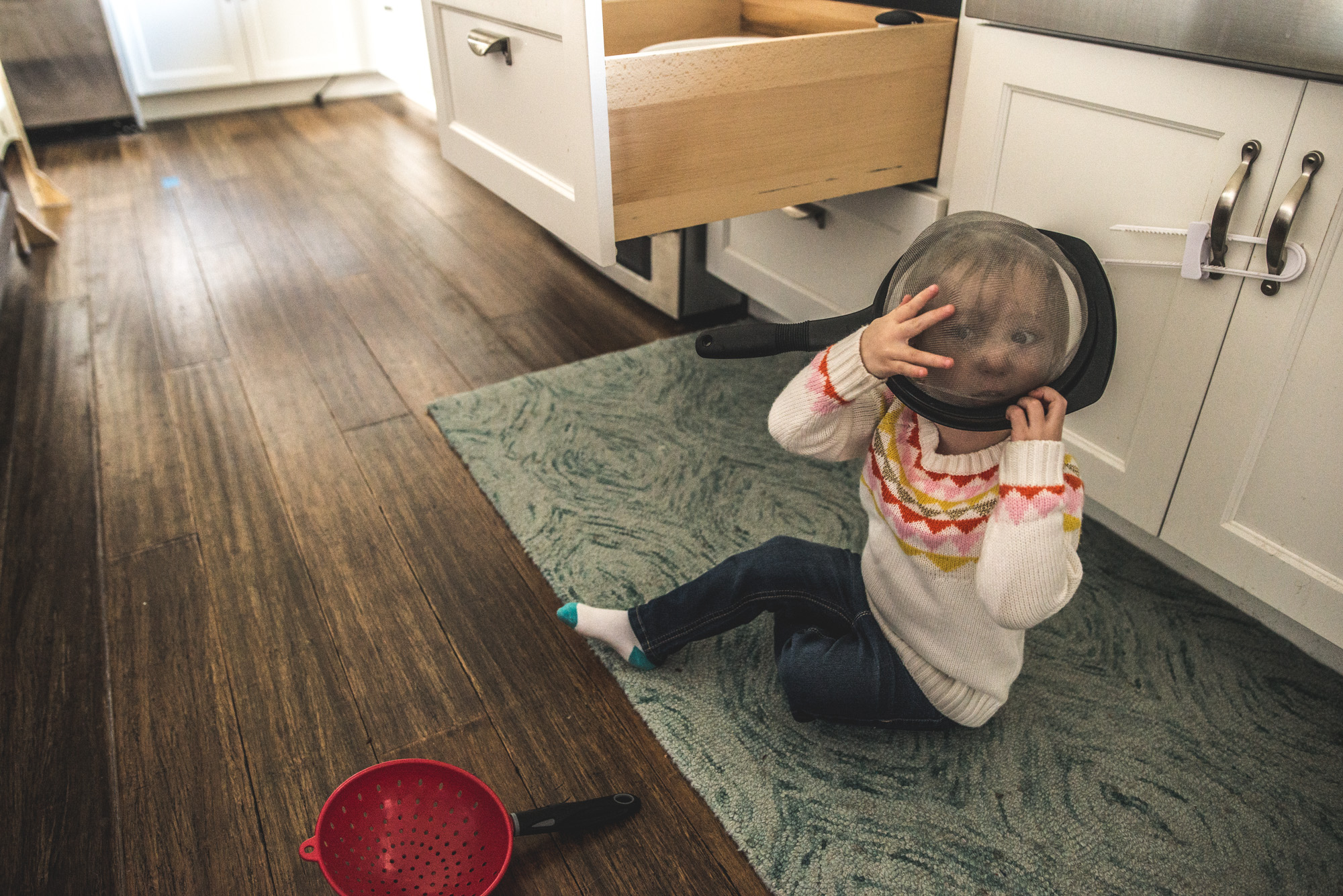 Little girl playing with a colander and putting it over her face during a day in the life documentary session in Denver, Colorado