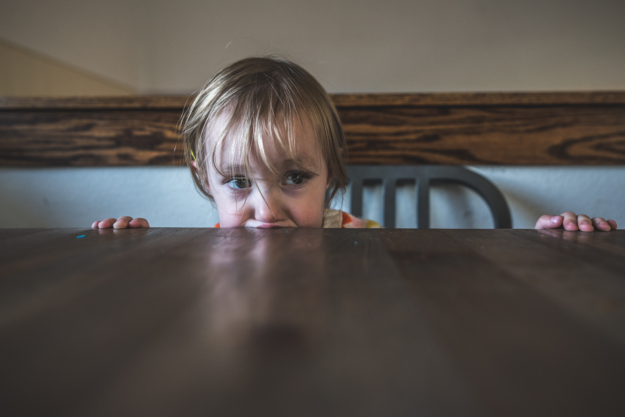 Close up of a little girl putting her mouth on the edge of the table during a half day in the life session in Denver, Colorado