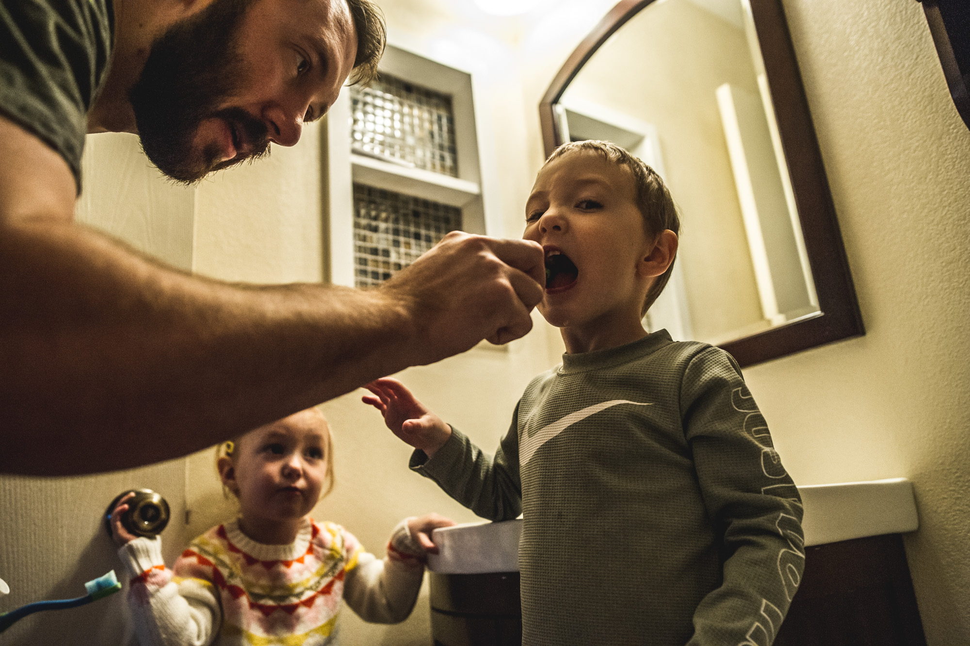 Father leans over to brush his young son's teeth as their young daughter looks on, color, Denver, Colorado