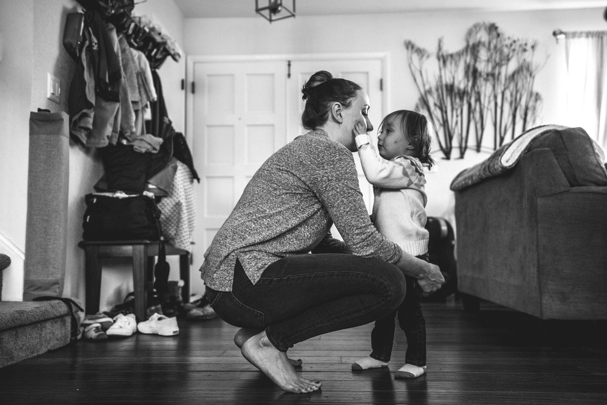 A mother leans down and her young daughter lightly touches her face, black and white, documentary family photography session, Denver, CO