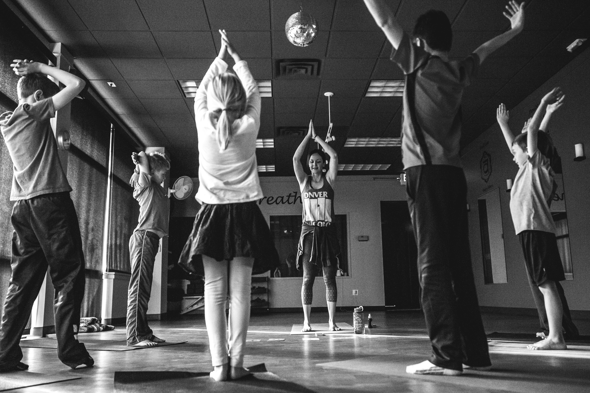 The whole class does a yoga pose with their hands over their heads during a yoga class for students with autism in Highland's Ranch, Colorado, black and white