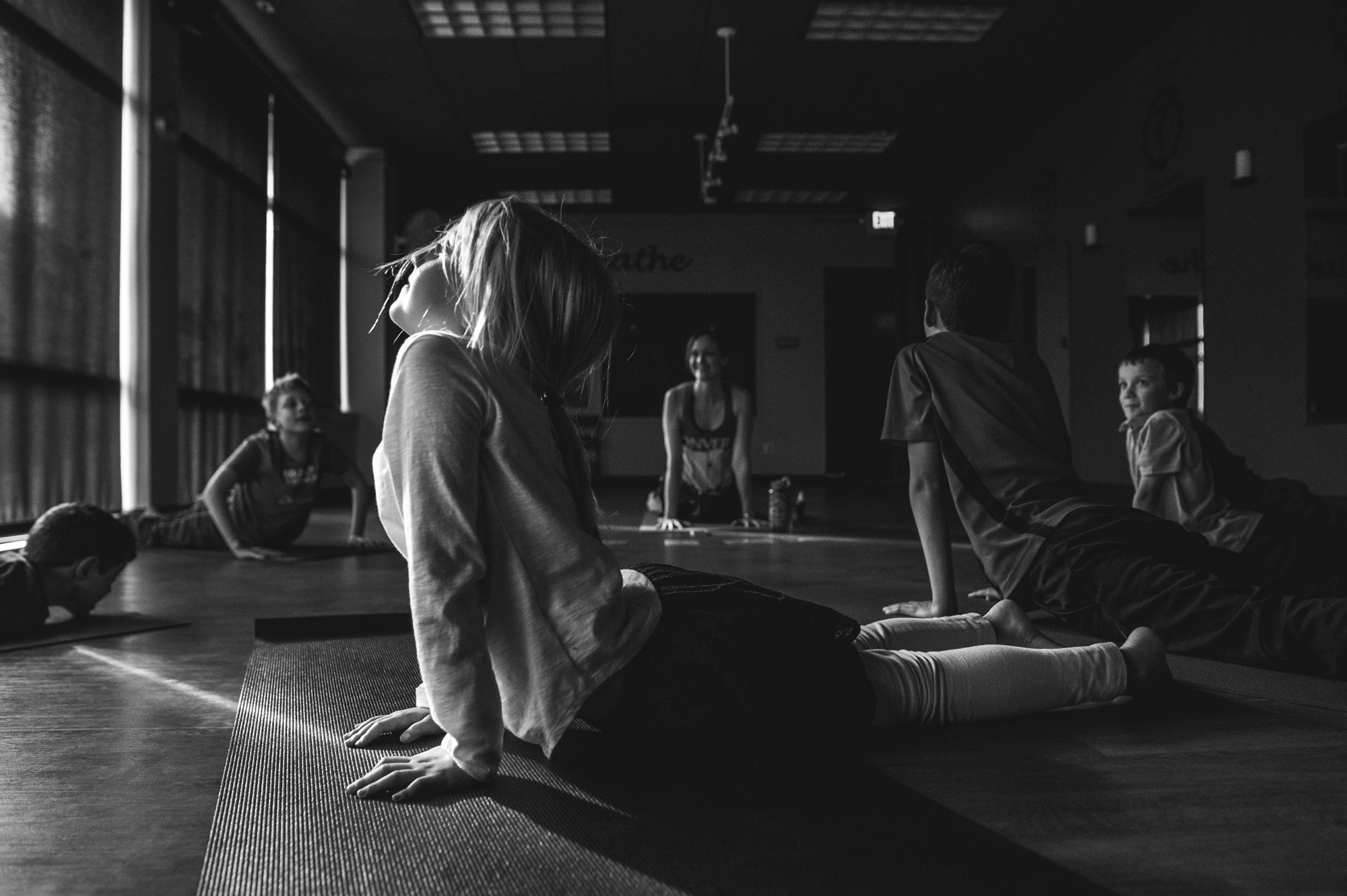 Class lays down and stretches their torsos upward during a yoga class, the little girl in the forefront with a perfect beam of light illuminating her profile, Highlands Ranch, CO, black and white