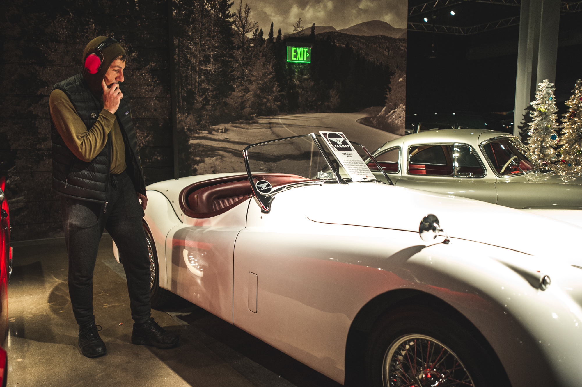 A man wearing red noise-cancelling headphones stands hand to chin, considering a bright white vintage automobile in the Vehicle Vault in Parker, Colorado during the Autism Society's Winter Fundraiser. Photo is in color.