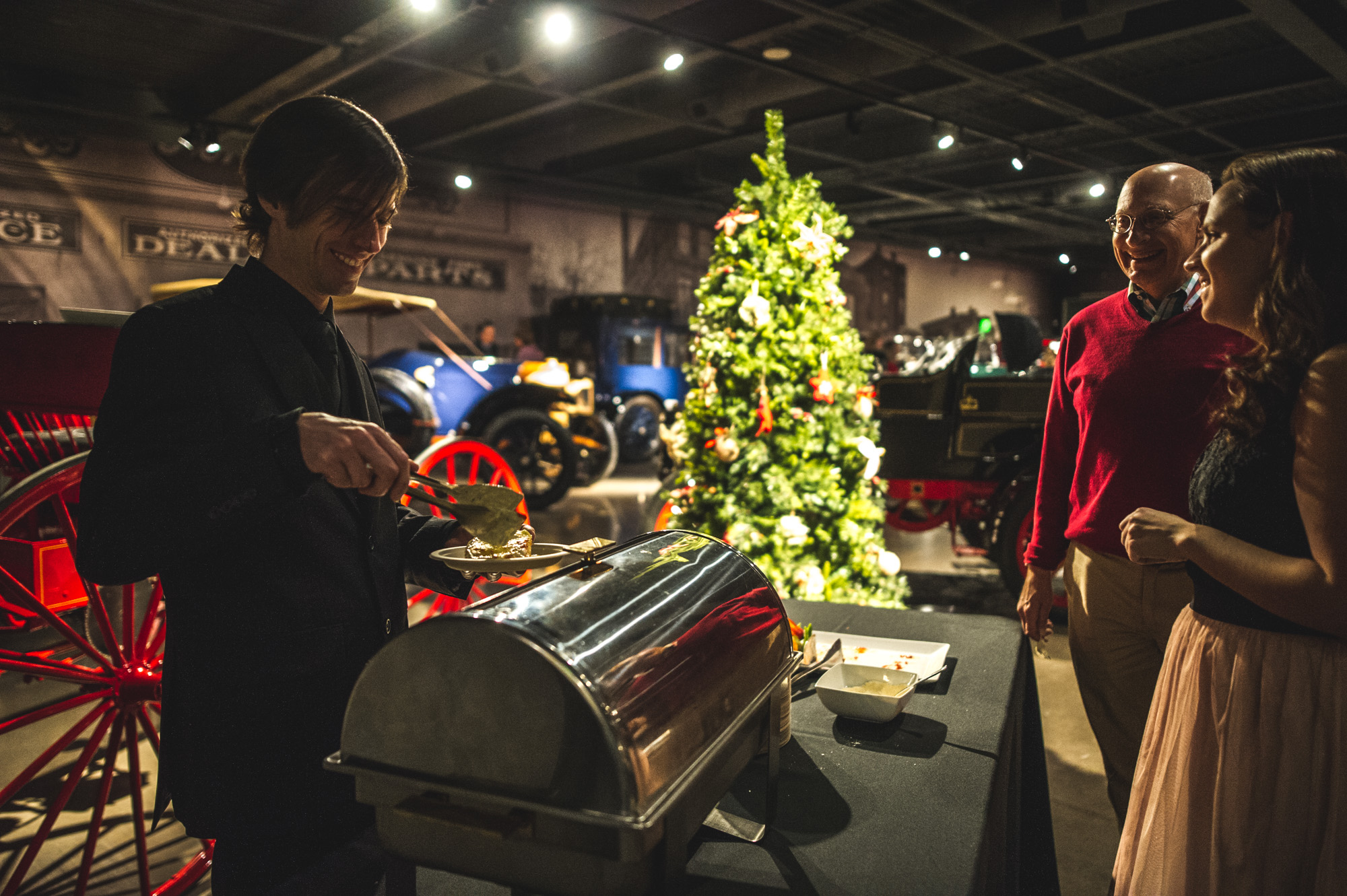 A man serves food to guests at the Autism Society Winter Fundraiser at the Vehicle Vault in Parker, Colorado. In the background are several vintage vehicles and a Christmas tree. Photo is in color.