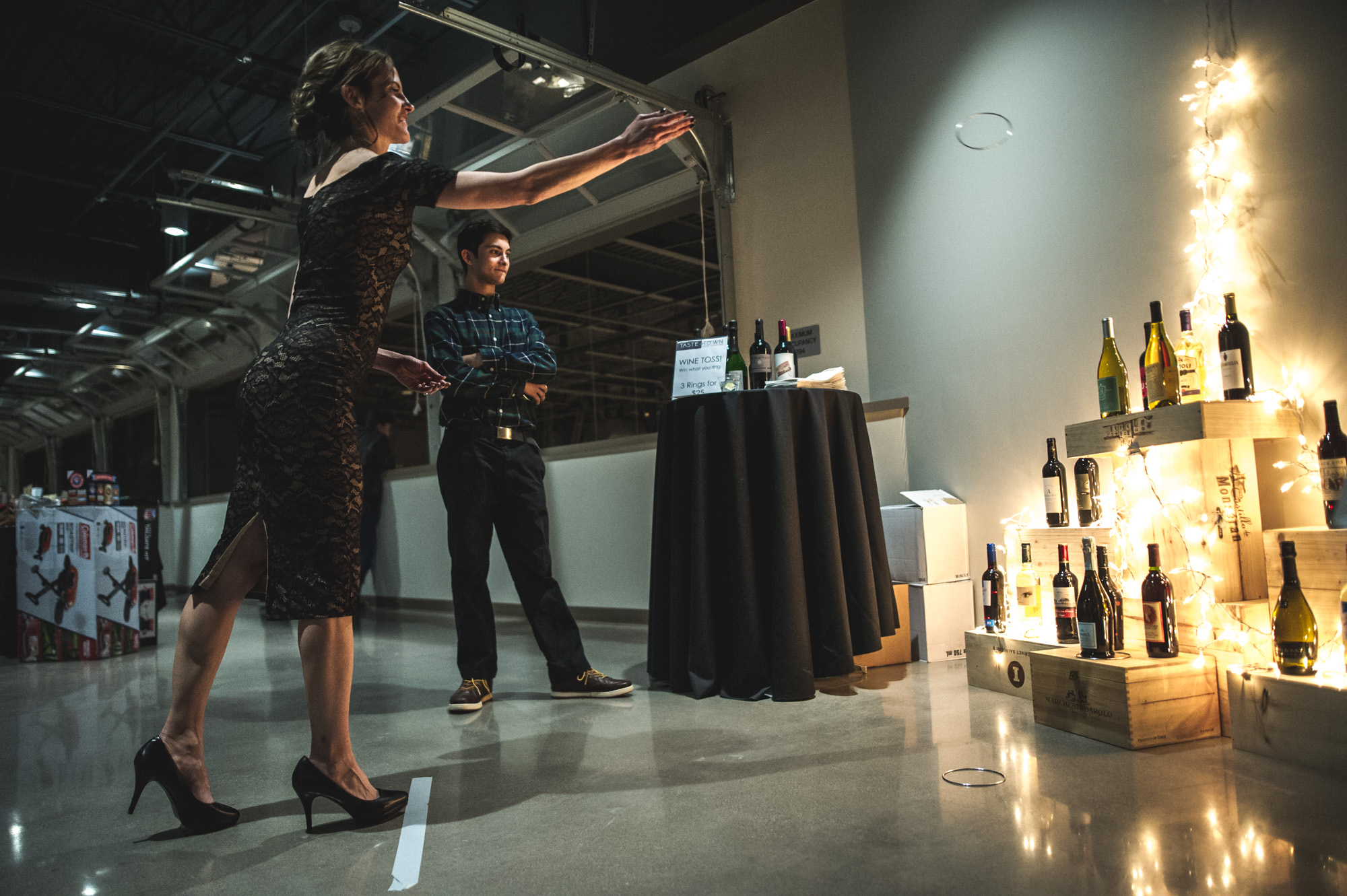 A woman in a cocktail dress and high heels throws rings at a wine display in hopes of getting one around a wine bottle as a man in the background watches. Photo in color.