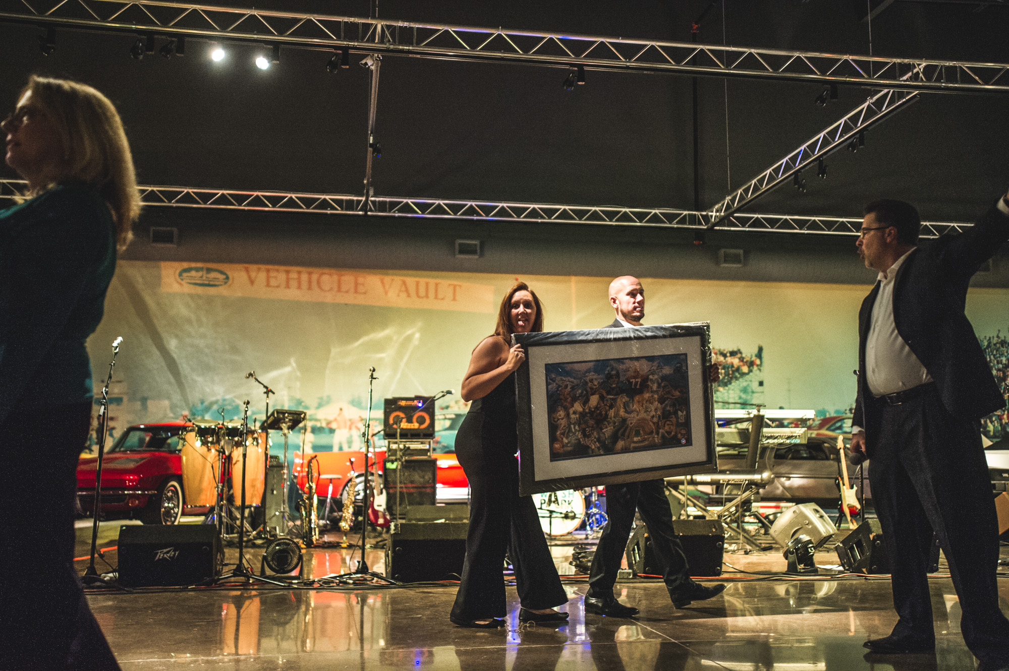 A woman and a man hold a giant framed auction item at the Vehicle Vault in Parker, Colorado. Color.