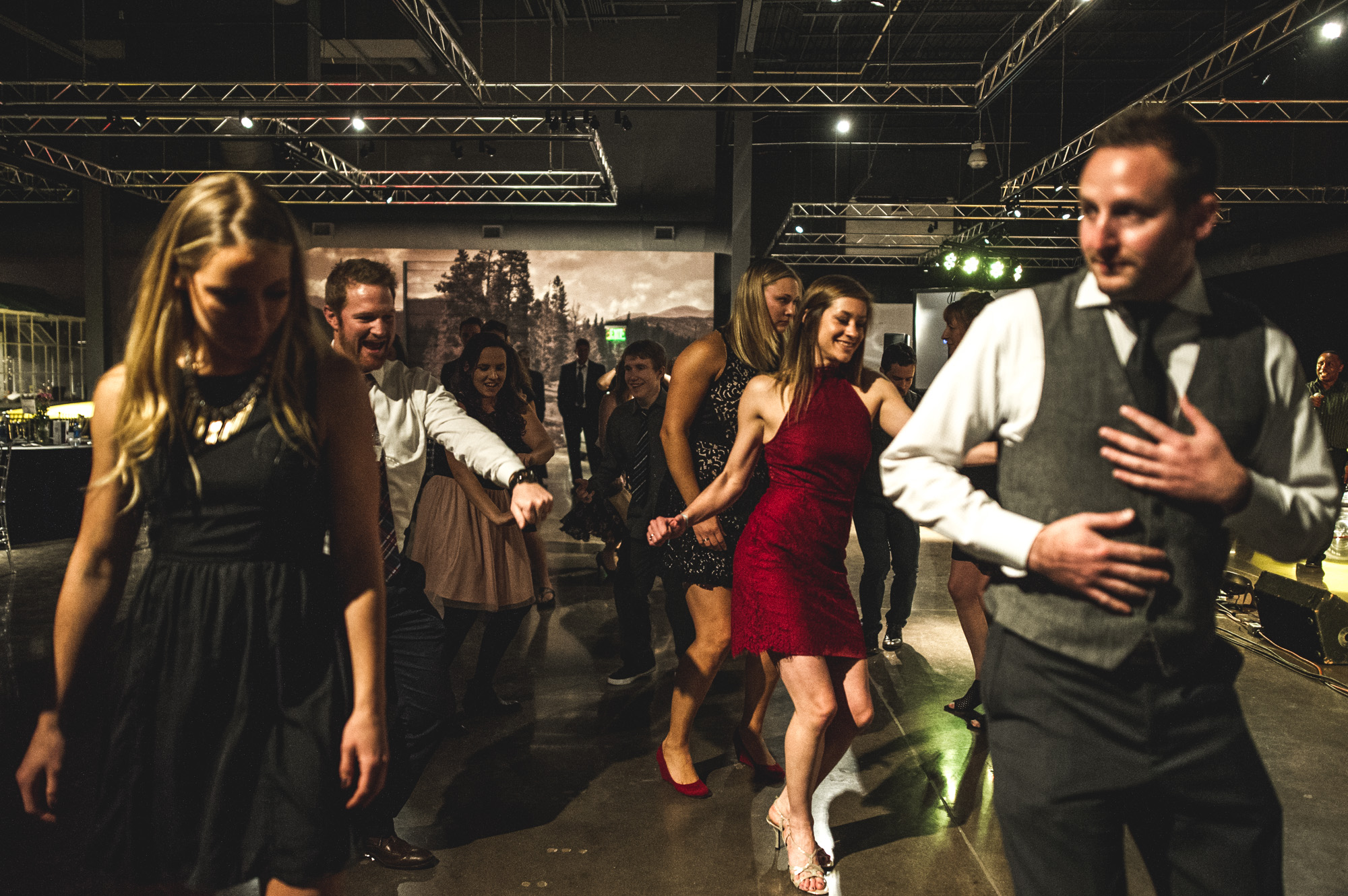 A group of guests at the Autism Society Winter Fundraiser at the Vehicle Vault do a line dance to the music of the Wash Park Band. Photo in color.
