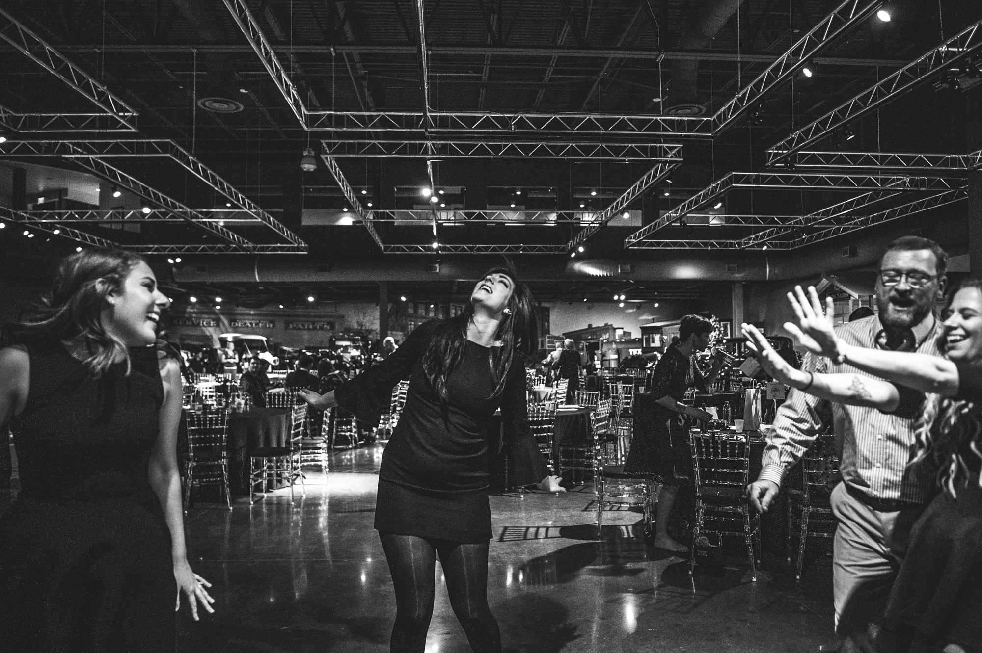 A group of people dances to the music in the Vehicle Vault in Parker, Colorado. Photo in black and white.
