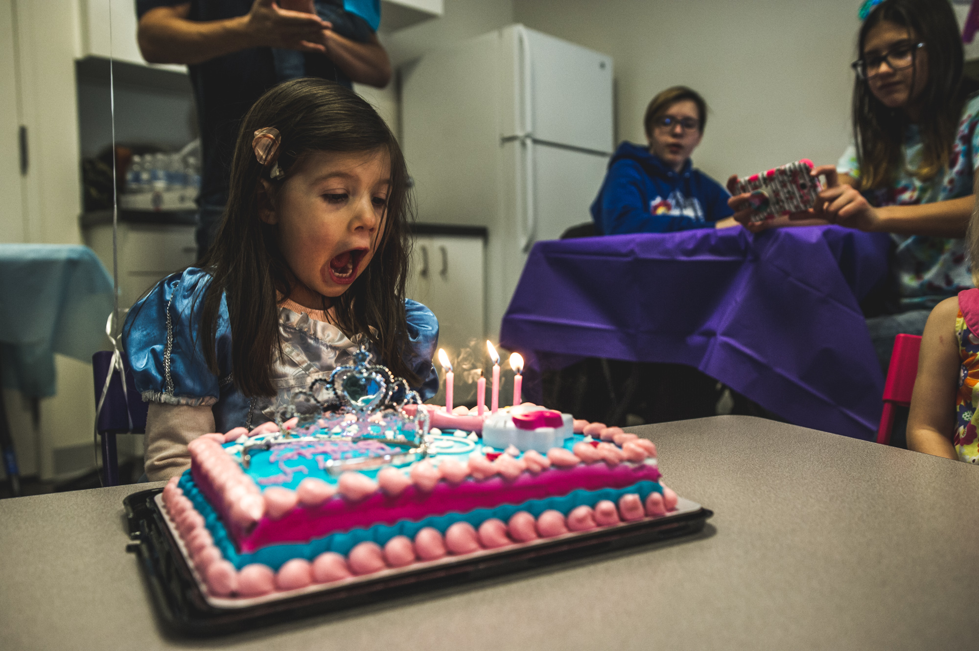 Little girl blows out four candles on her pink and blue birthday cake as she wears a princess dress at her birthday party at Family Connections kids' gym in Littleton, Colorado