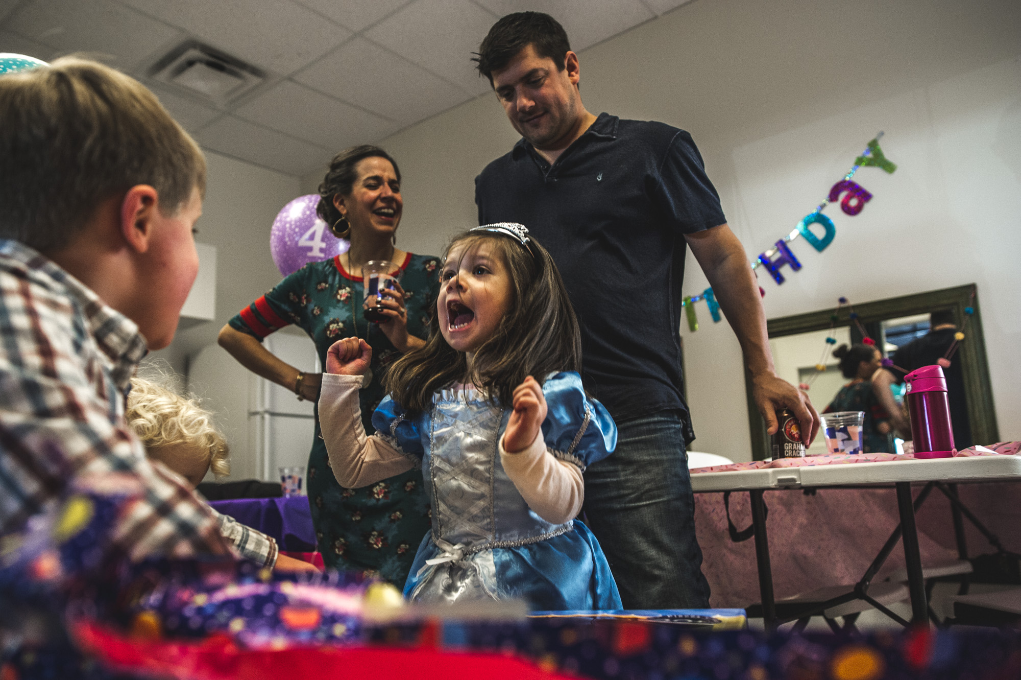A little girl jumps for joy as her parents look on. The little girl is wearing a princess dress and crown and is celebrating her birthday at Family Connections kids' gym in Littleton, Colorado. Photo is in color.
