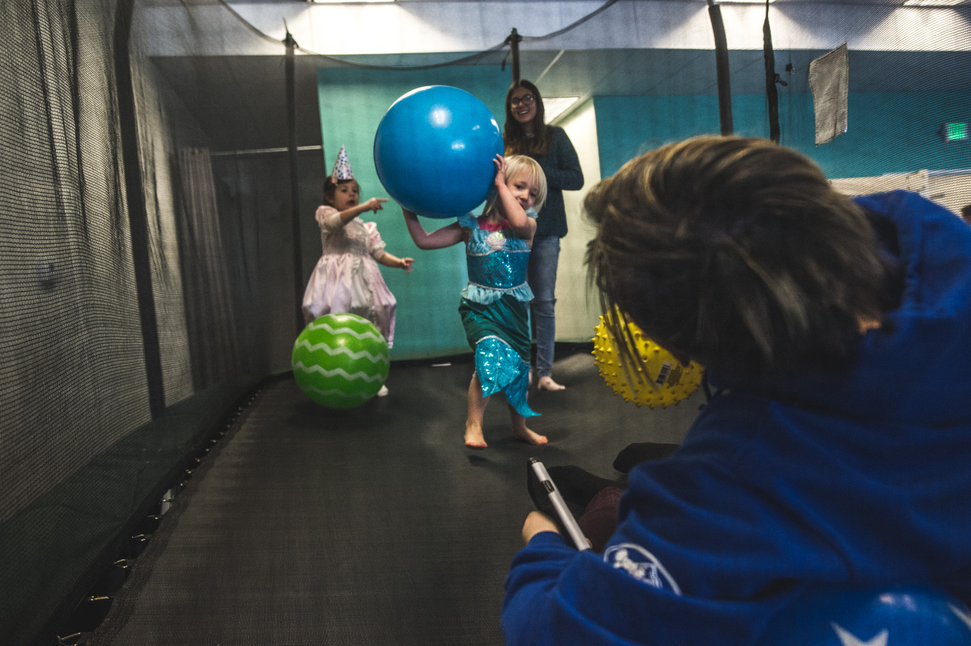 Four people are on a trampoline, 2 younger kids and 2 bigger kids, and one of the smaller children takes aim at one of the bigger kids with a large blue ball at a kids' gym in Littleton, Colorado.