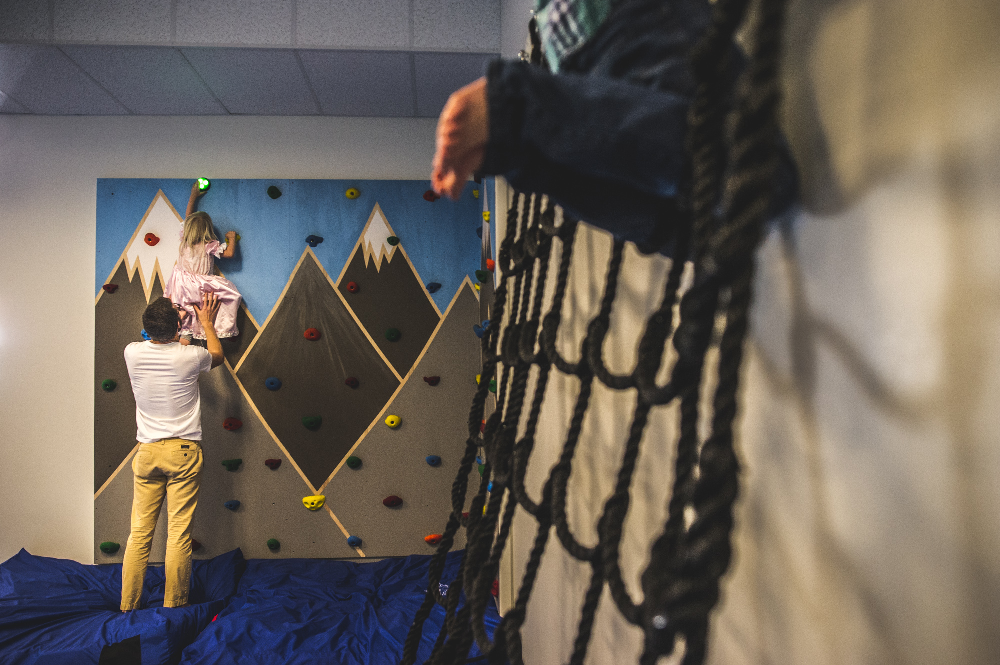 A young girl climbs a rock wall with the help of her dad while wearing a pink princess dress. In the foreground to the right can be seen the legs of a little boy climbing a net. Littleton, Colorado.