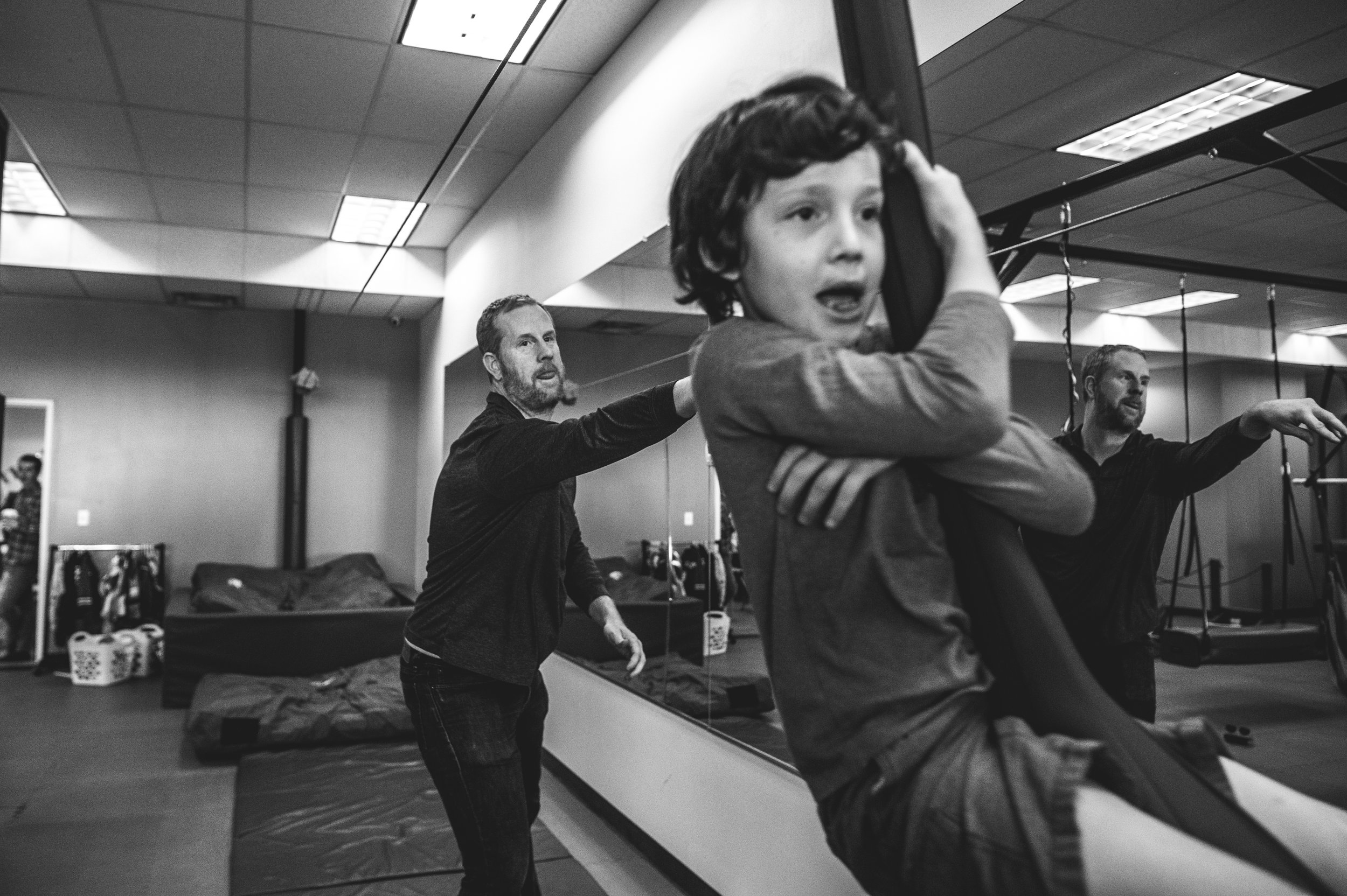 Black and white photo of a father pushing his son on a zipline at the Family Connections kids' gym in Littleton, Colorado