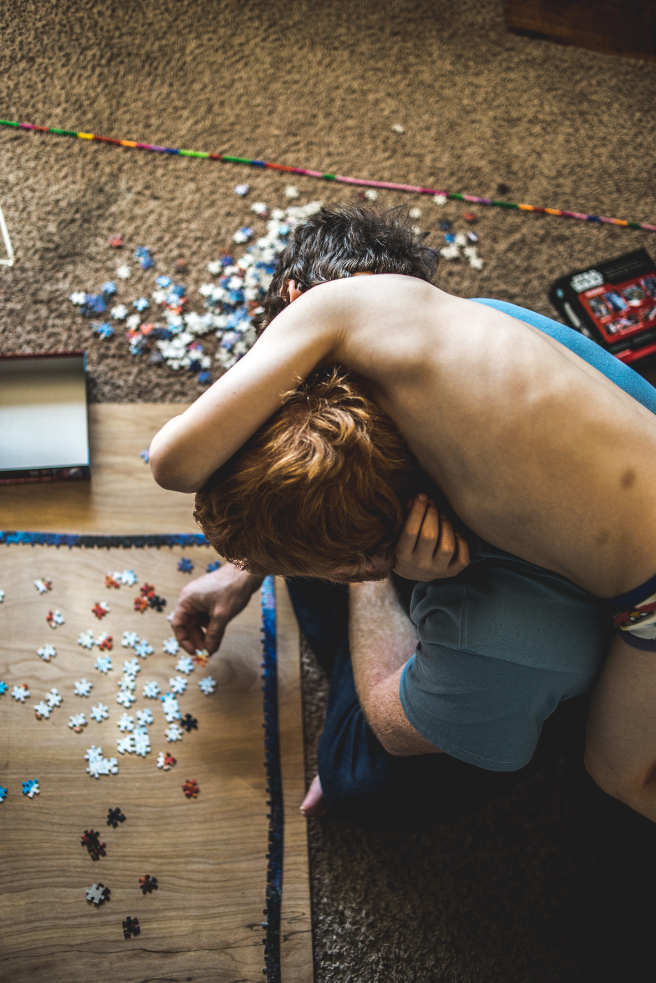 Color photo of a little boy climbing on his dad's back as his father attempts to put together a jigsaw puzzle