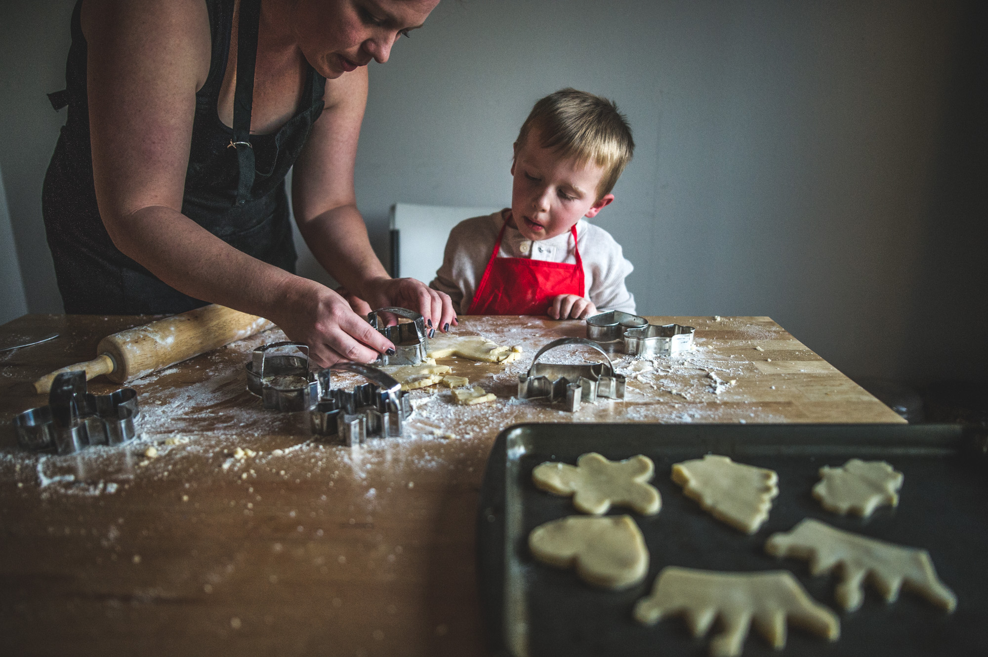 Color photo of a mother and son wearing aprons and making Christmas cookies together in Aurora, Colorado