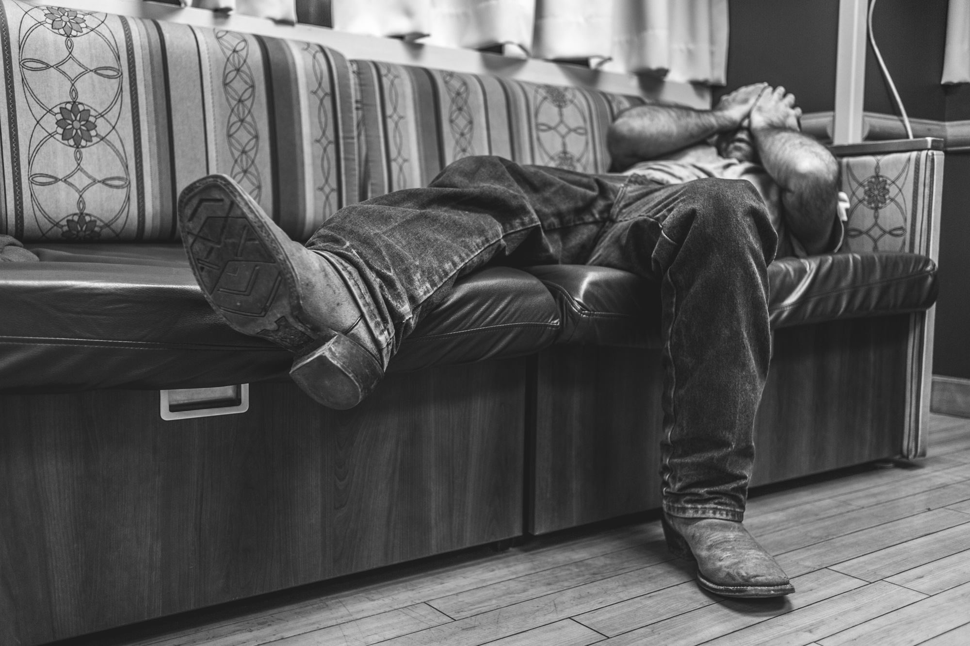 Black and white photo of an expectant father lying on the couch, waiting for the birth of his child, and rubbing his eyes in exhaustion