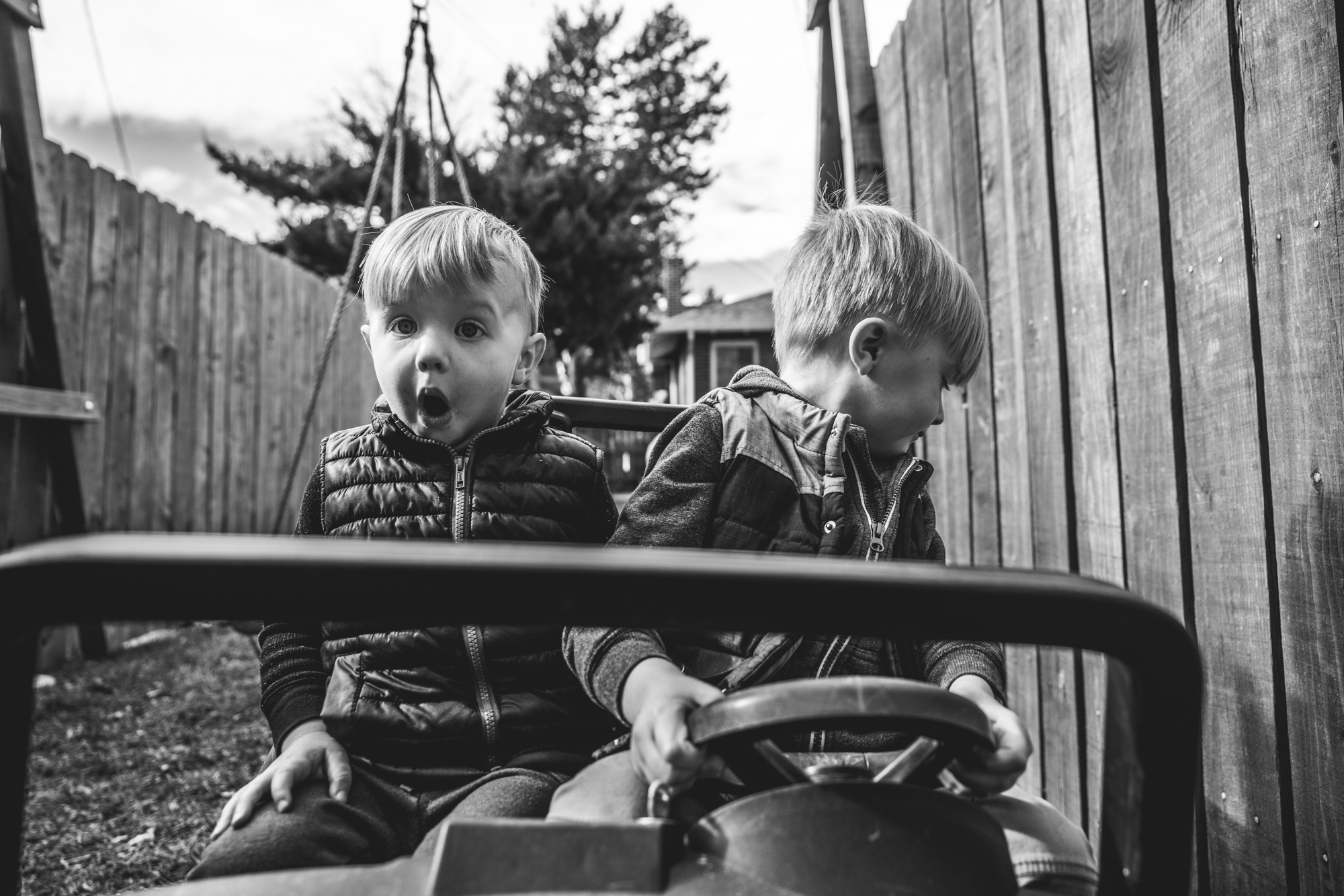 Black and white photo of two boys sitting in their toy jeep in their back yard in Park Hill, Colorado. The driver looks behind him to back up while his brother has a shocked look on his face.