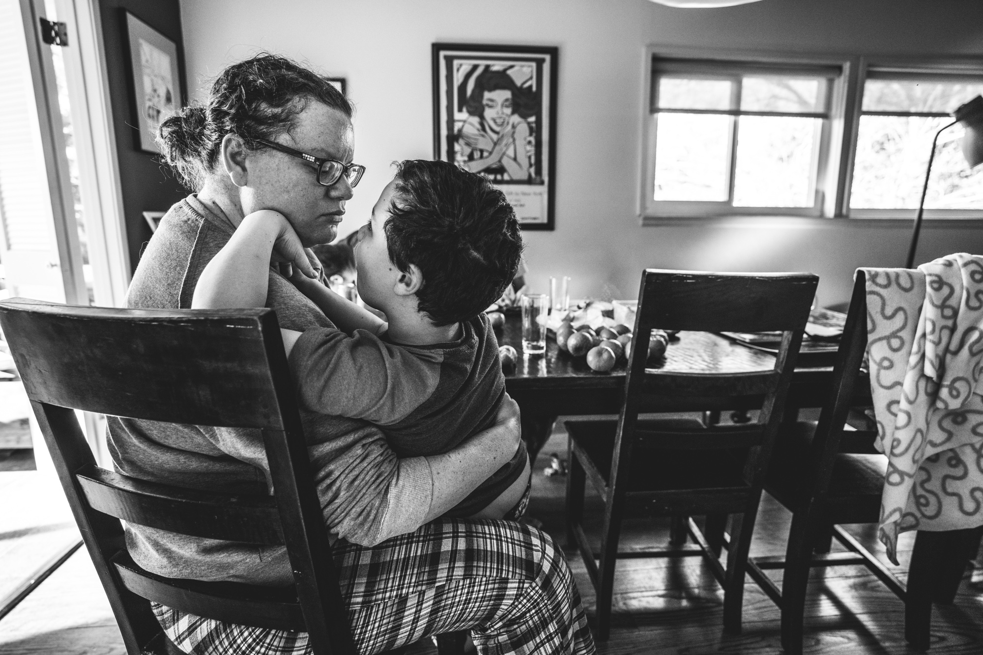 Black and white photo of a mother looking lovingly at her son who is sitting on her lap at the breakfast table during their documentary family photography session