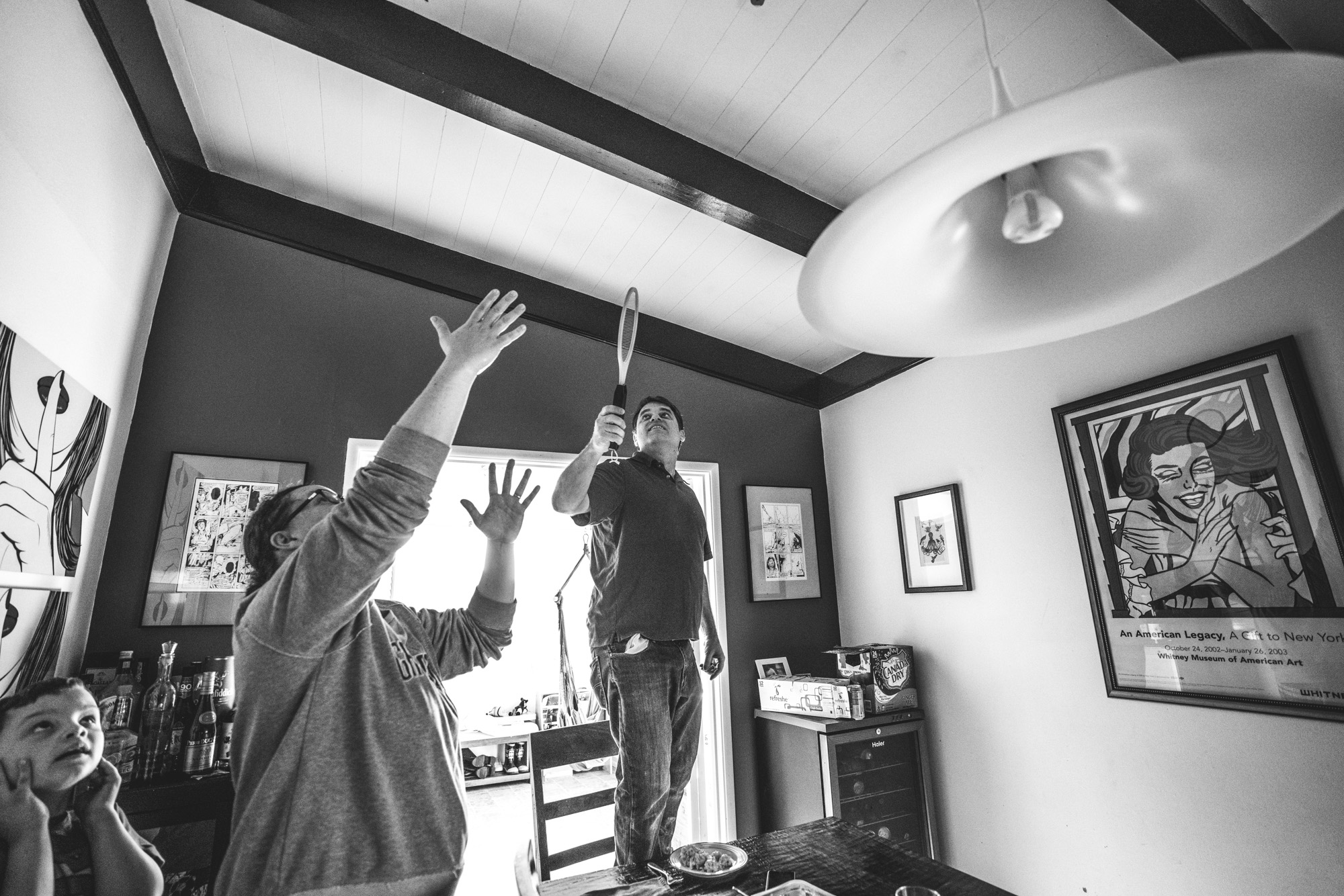 Black and white photo of a mother pointing to the ceiling as her husband stands on a chair holding an electric fly zapper, searching for the fly to kill. Photo taken during their family photography session in Oakland, California.