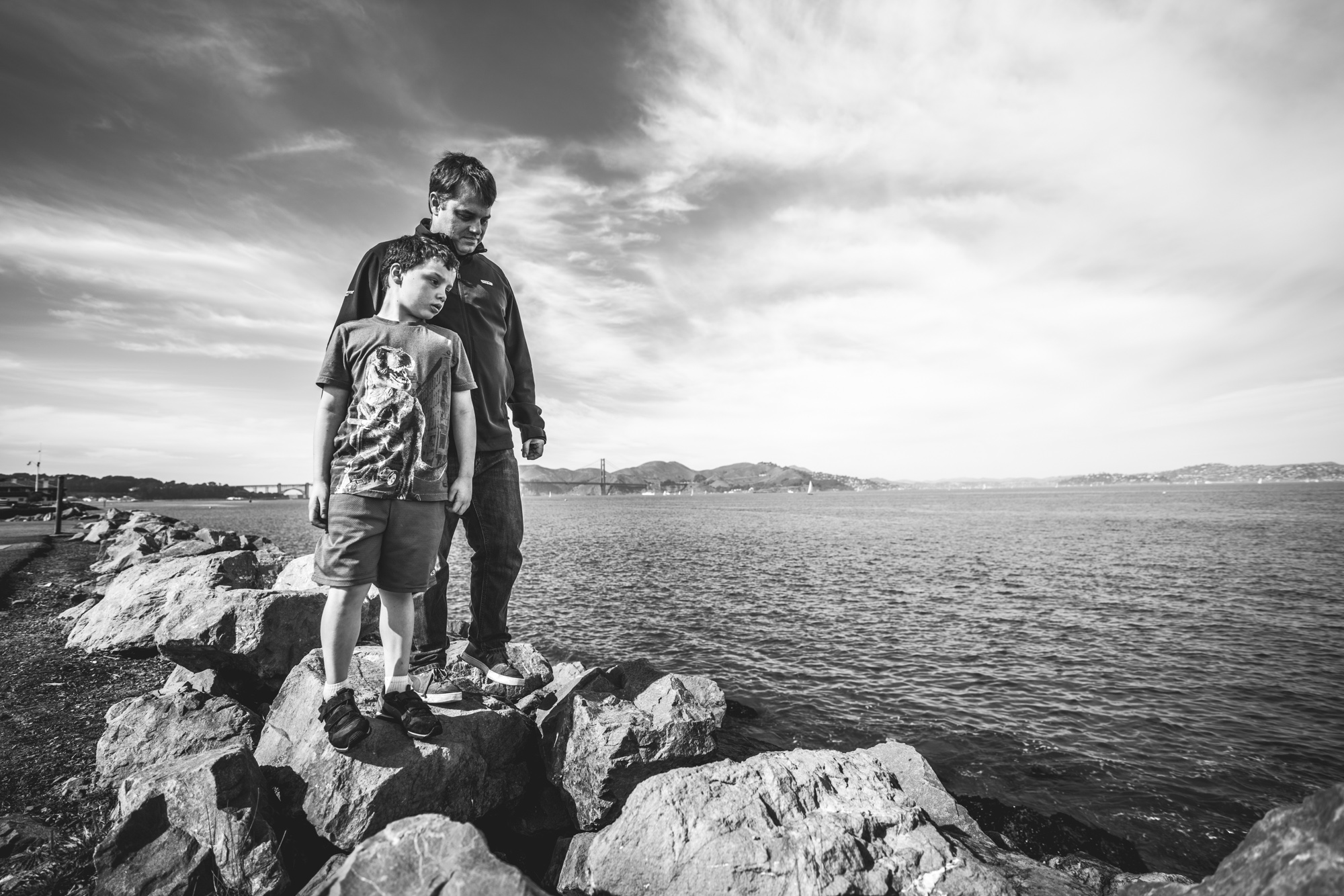 Black and white photo of a father and son standing atop large boulders lined up in front of the San Francisco Bay during their family photography session