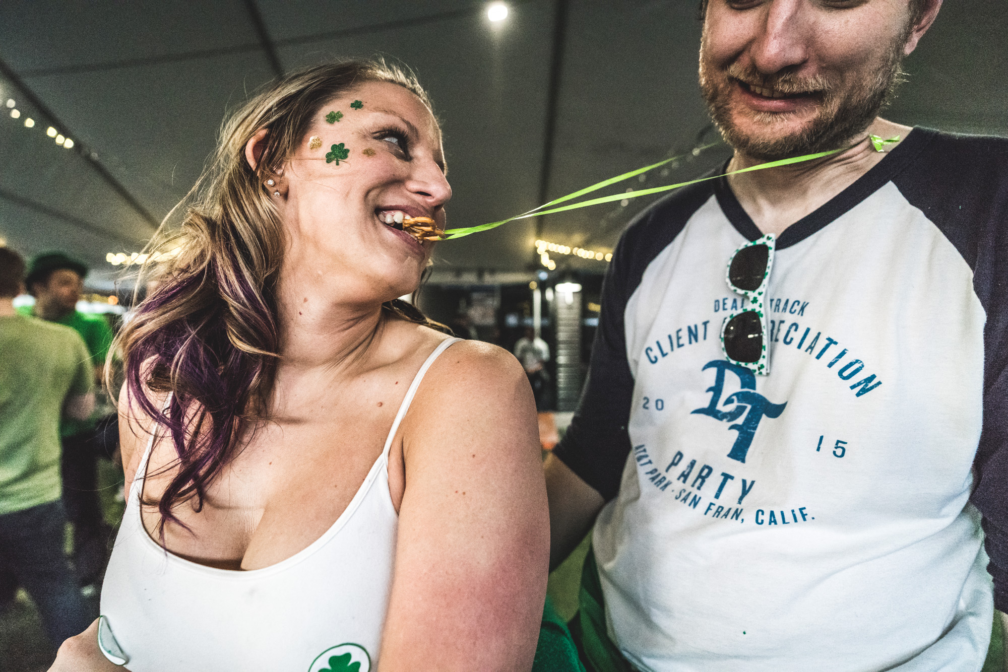 Color photo of a couple on a dance floor wearing wearing various St. Patrick's day accoutrements. The man wears a green ribbon on his neck like a necklace as the woman he's dancing with attempts to eat off the pretzel dangling off of it. The woman looks back at the man jokingly. Taken at the ViewHouse in downtown Littleton, CO.