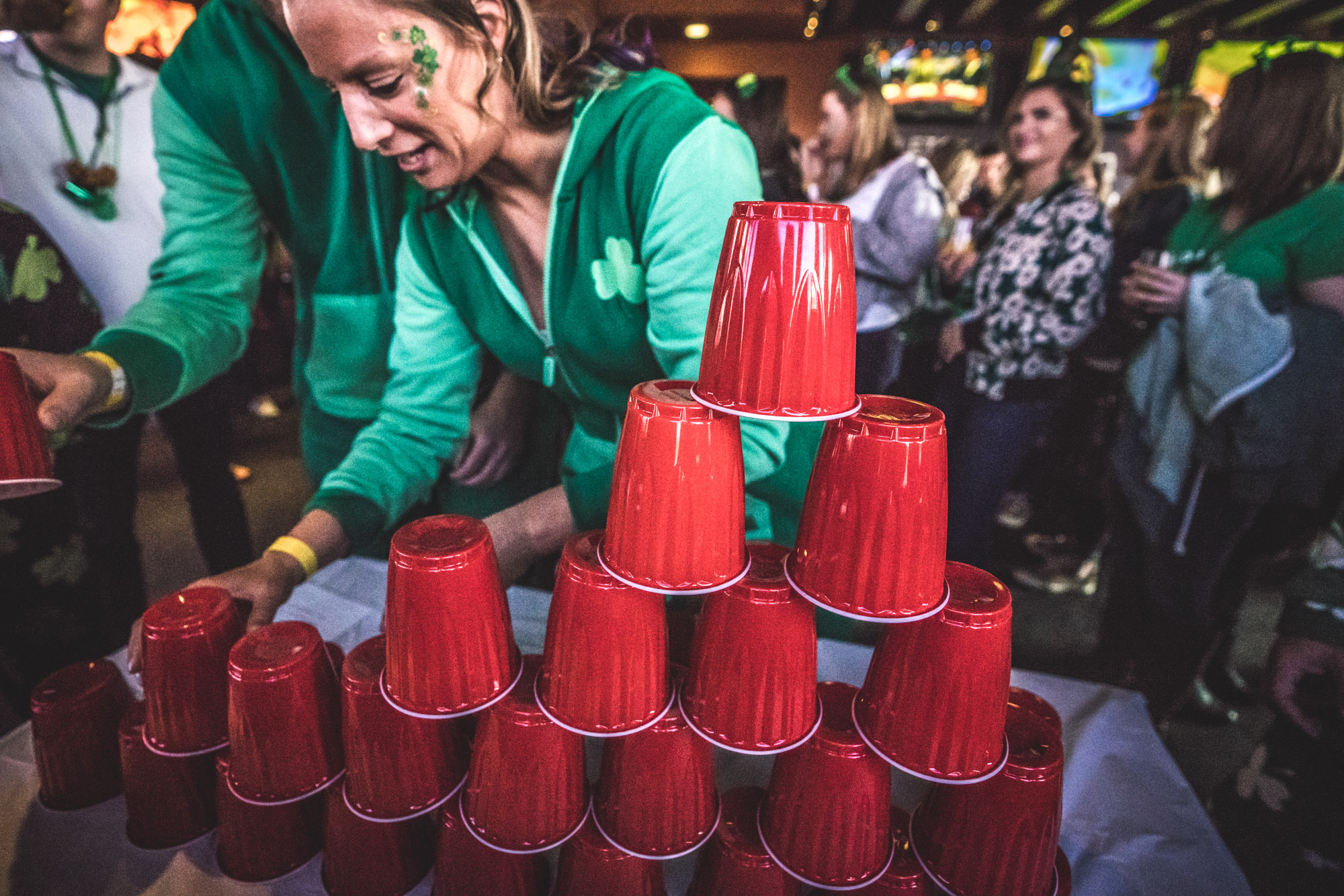 Color photo of a couple wearing St. Patrick's Day onesies trying to stack red solo cups. Photo taken at the original Colorado Tavern in downtown Littleton during the Autism Society of Colorado's Shamrock Stumble fundraiser.