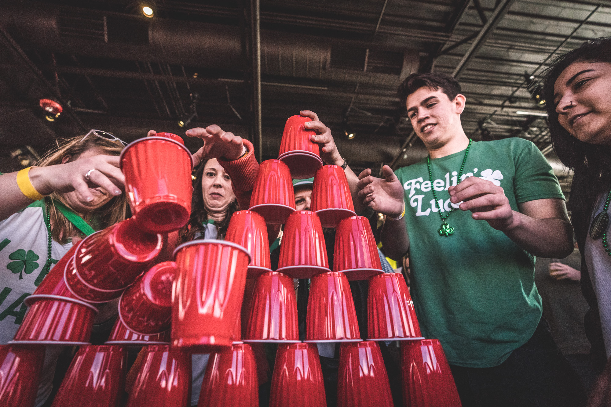 Color photo of a group of people attempting to stack red solo cups at the ASC Shamrock Stumble pub crawl fundraiser for Saint Patrick's Day in Littleton, CO.