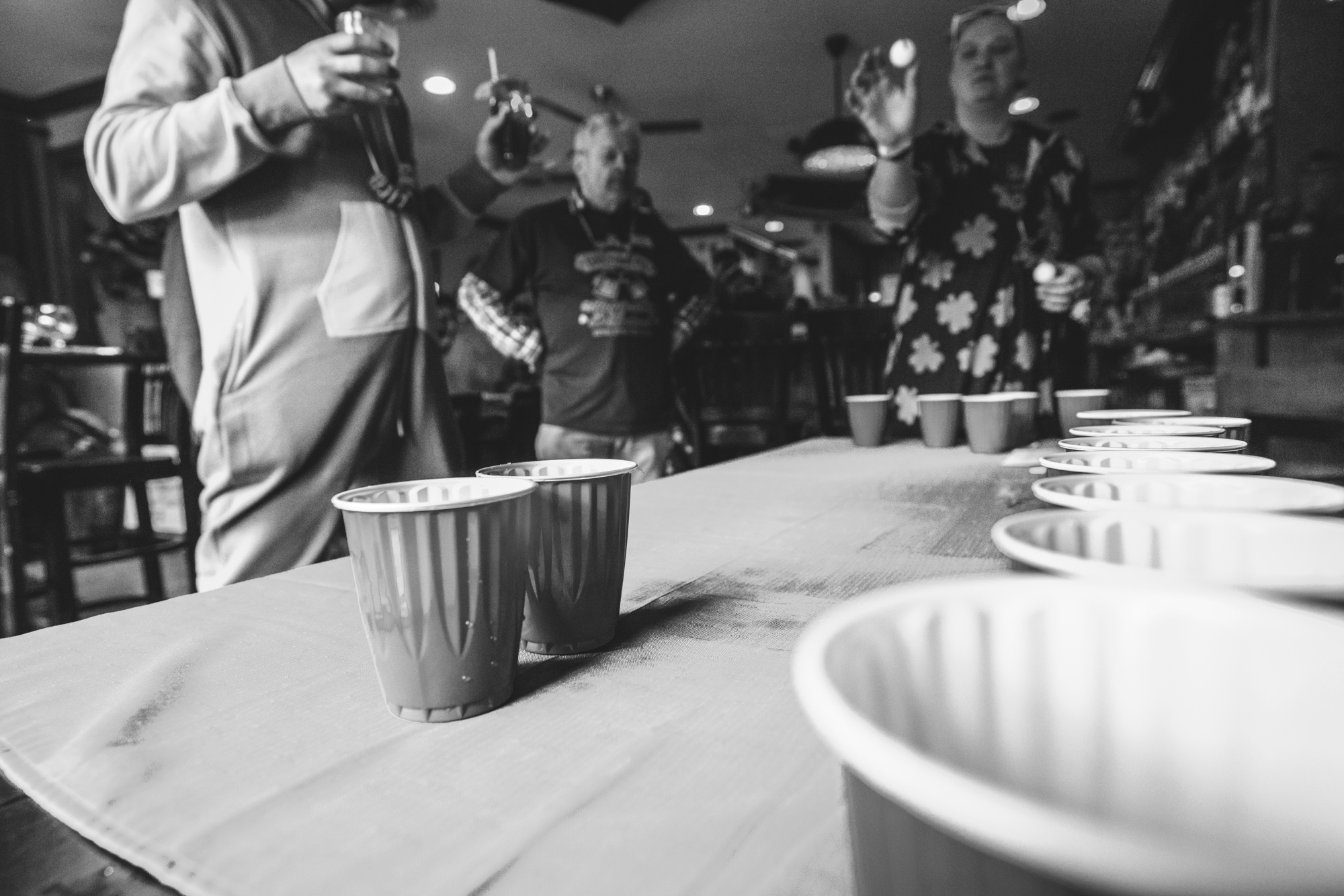 Black and white photo of a woman taking careful aim with a ball at two solo cups on a table as she plays Beer Pong at Jake's Brew Bar during the documentary photography session of the ASC Shamrock Stumble.