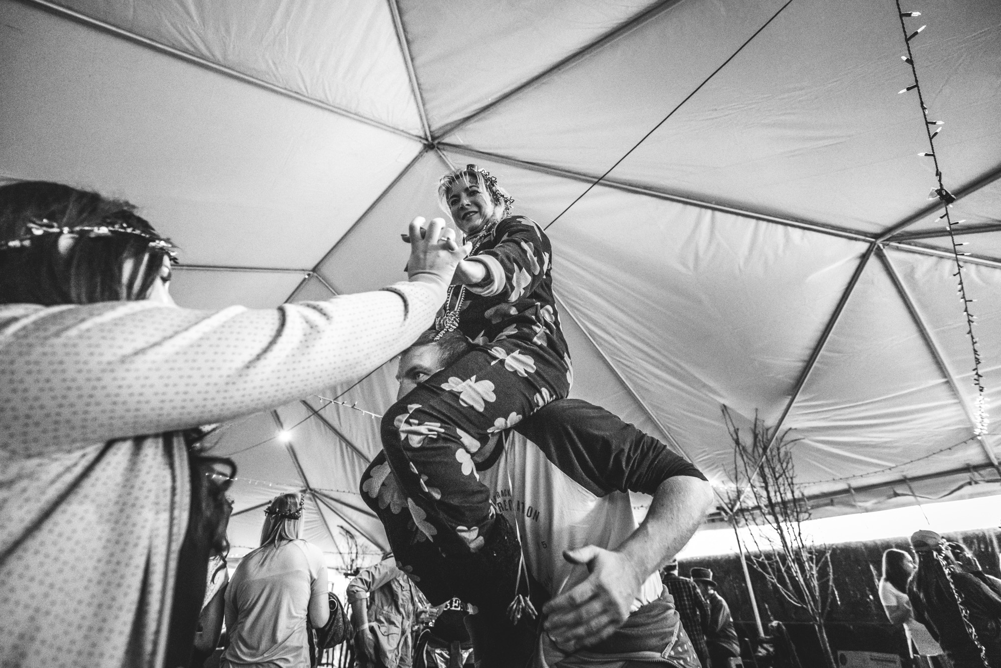 Black and white photo of a woman attempting to climb onto a man's shoulders as they party during the ASC Shamrock Stumble fundraiser event in Littleton, CO.