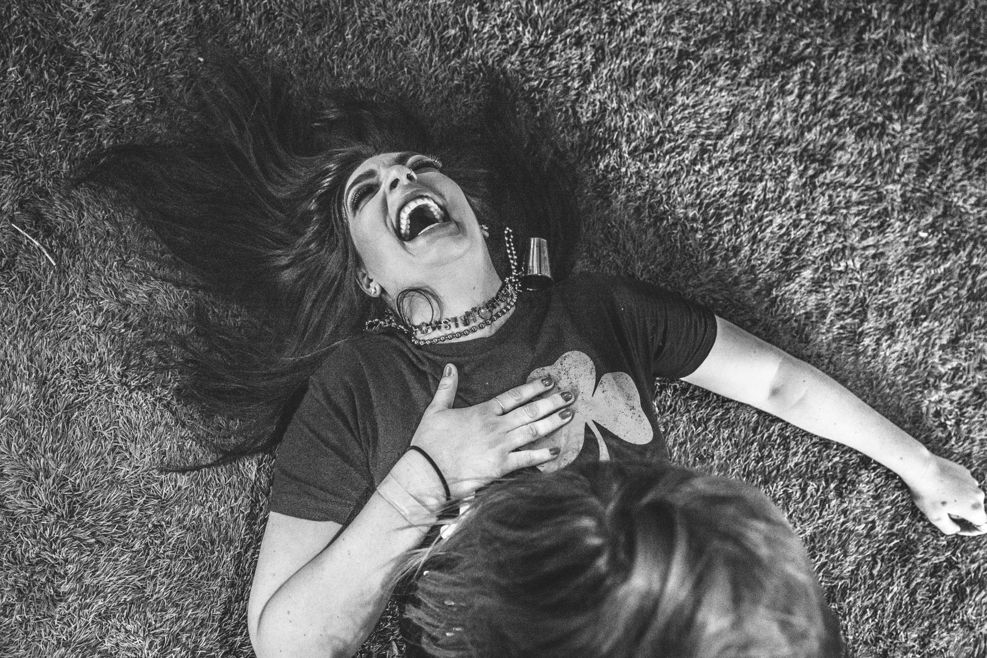 Black and white photo of a young woman lying on the ground laughing hysterically during a dance party at the Autism Society of Colorado Shamrock Stumble fundraiser.