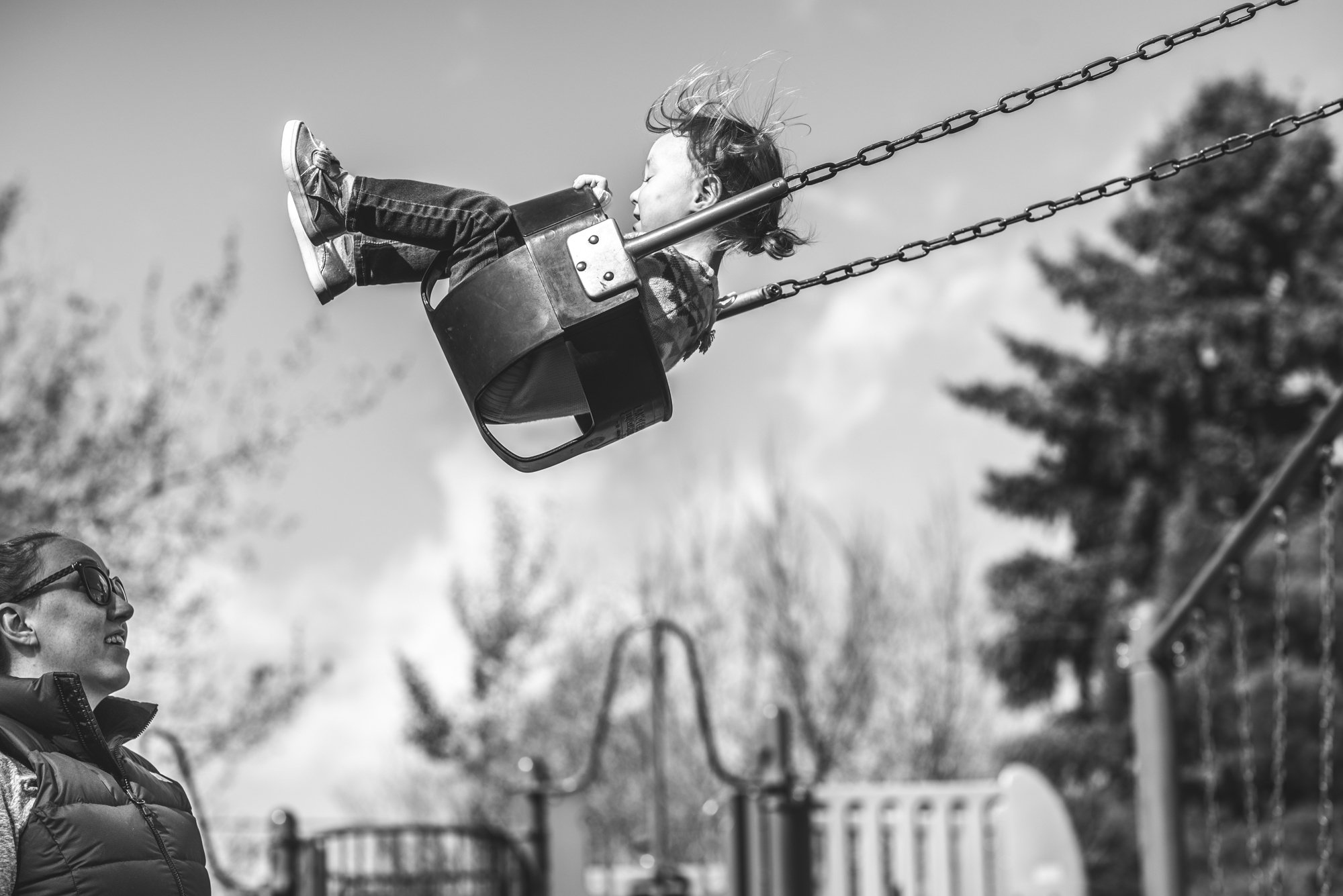 Black and white photo of a little girl swinging high on a swing as her mother watches from below