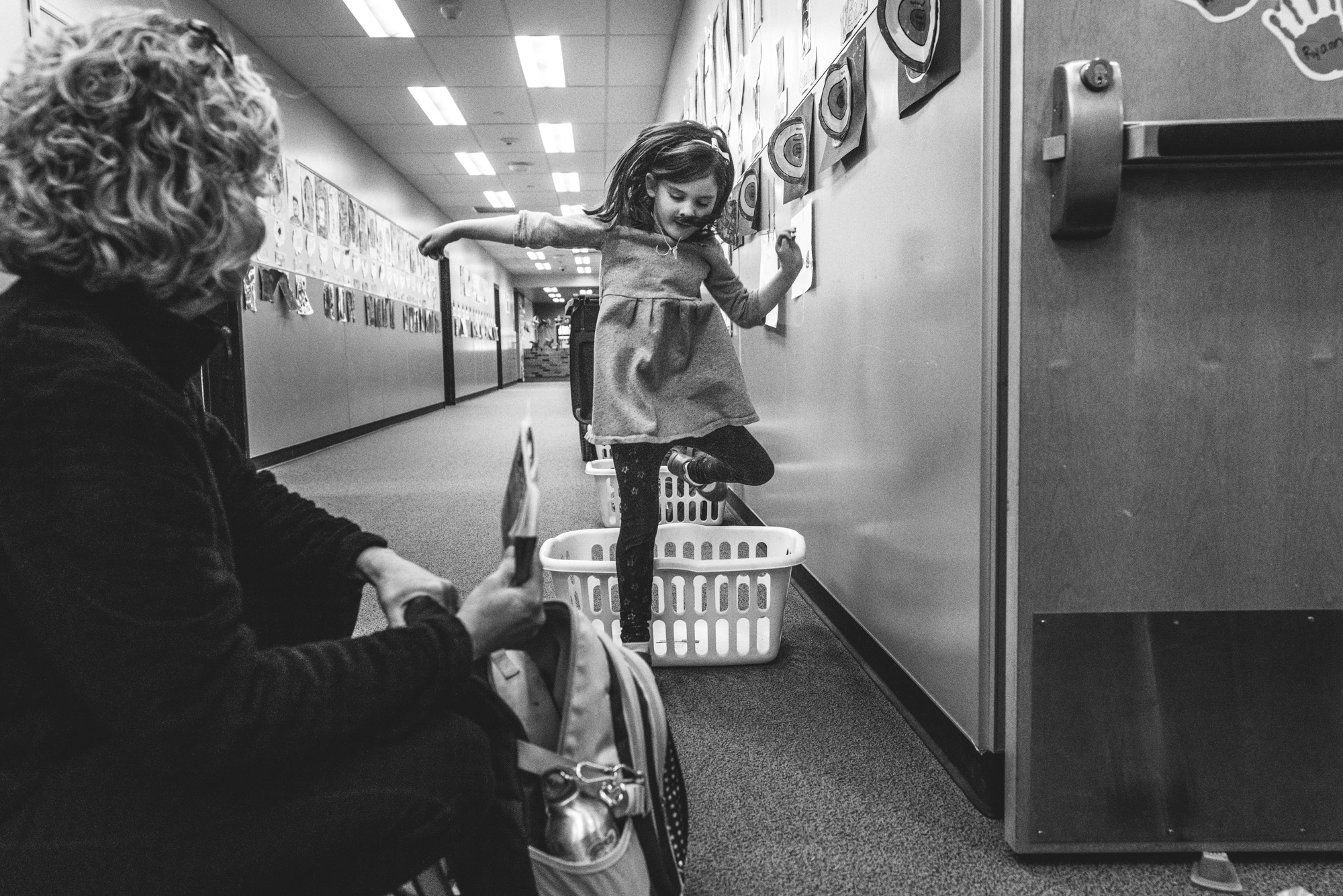 Black and white photo of a little girl jumping over a basket in a hallway at her school as her mother watches on during their day-in-the-life photography session