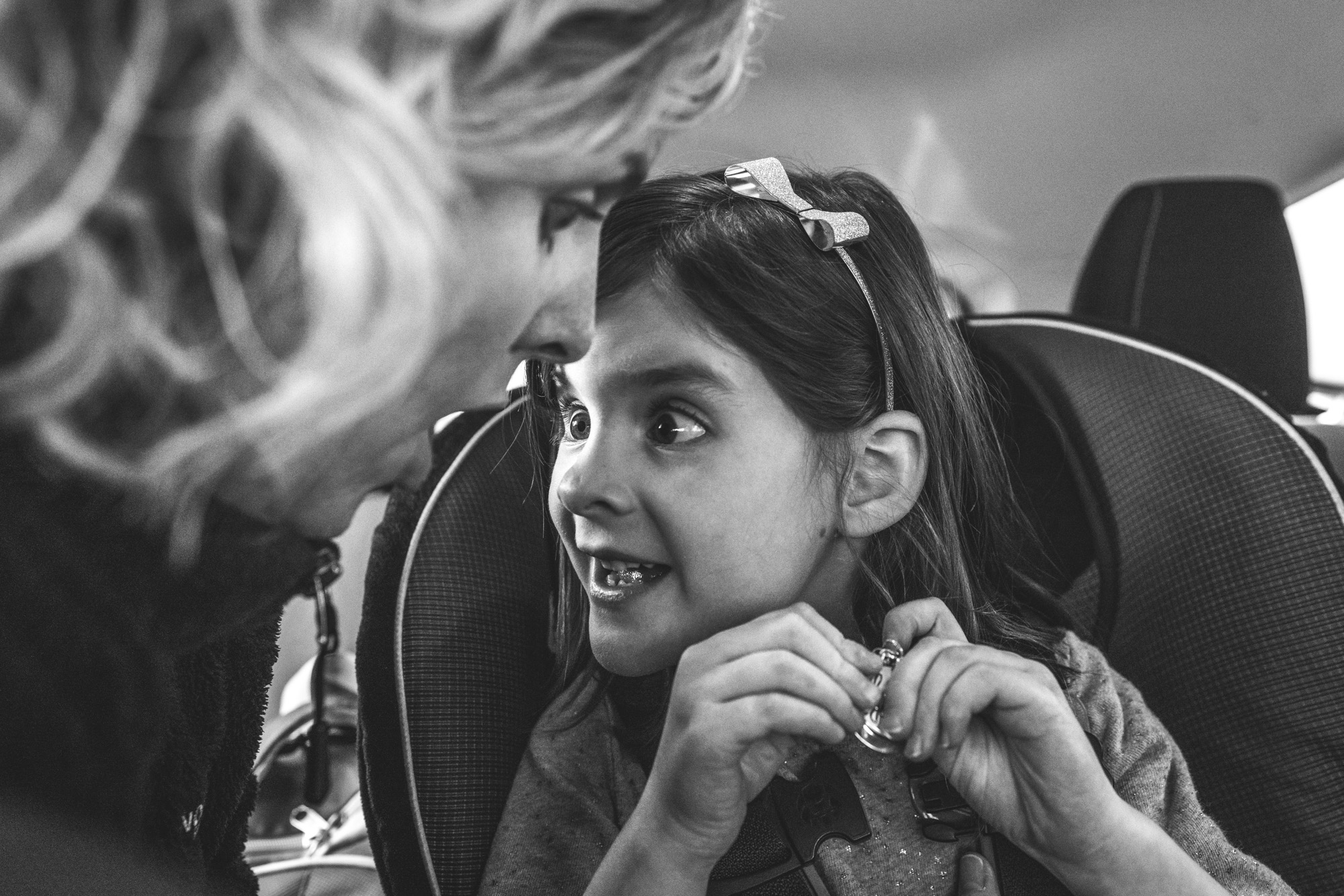 Black and white close-up photo of a little girl in a car seat telling her mother a secret while her mother reacts with a shocked face. Photo taken during the family's documentary photography session in Denver, Colorado.