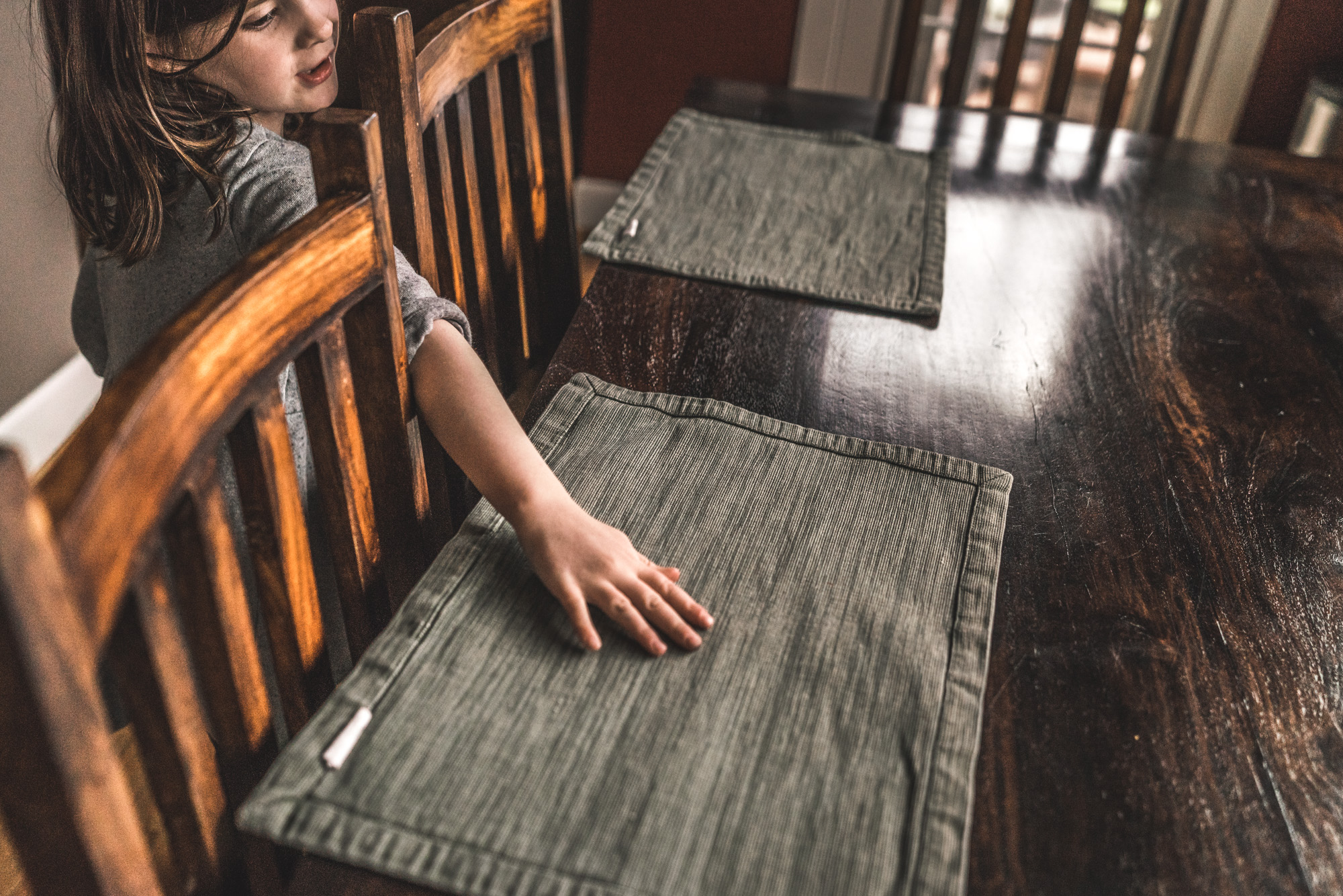 Color photo of a little girl laying out placemats for dinner. Photo taken in Stapleton, Colorado during her family's in-home photography session.