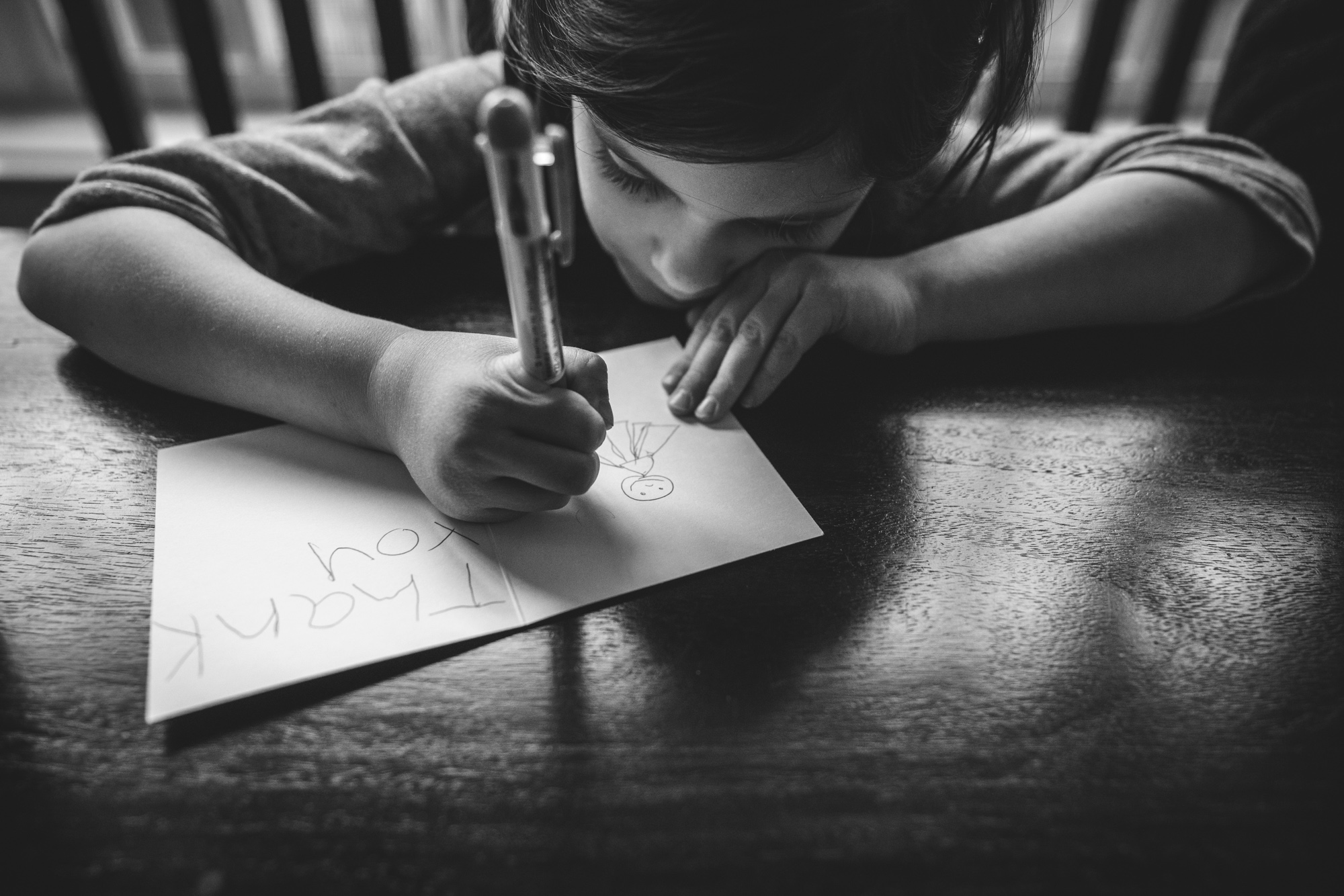 Black and white photo of a sweet little girl writing out a thank-you card and drawing a picture of a ballerina. Taken at her kitchen table in Denver, Colorado during her family's at-home photography session.