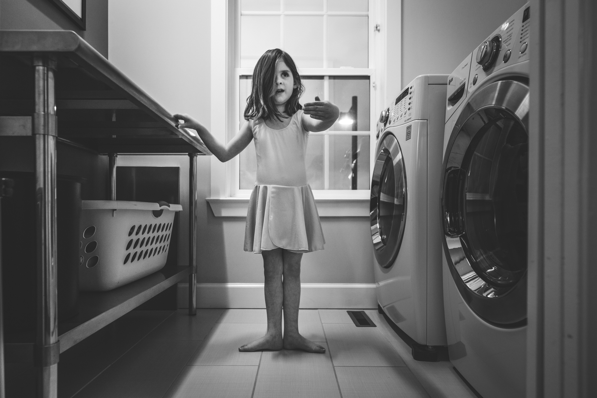 Black and white photo of a 6-year-old girl in her ballet costume doing one of the ballet positions while standing in her laundry room in her home in Stapleton, Colorado. Taken during her family's documentary photography session.