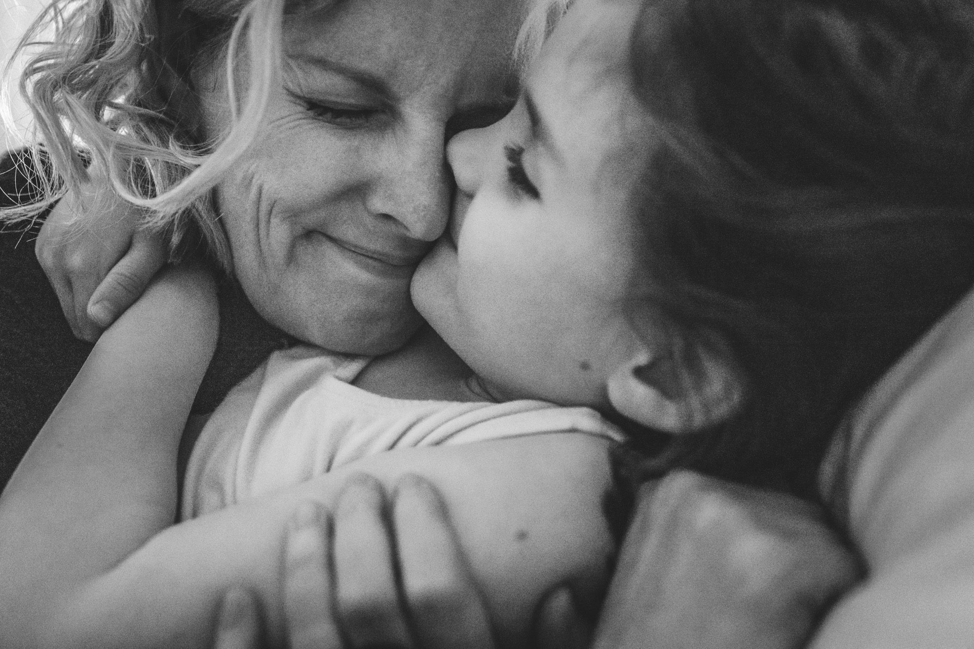 Black and white super close-up photo of a mom and her 6-year-old daughter hugging each other and smiling lovingly. Taken at their home in Stapleton, Colorado during their in-home photography session.