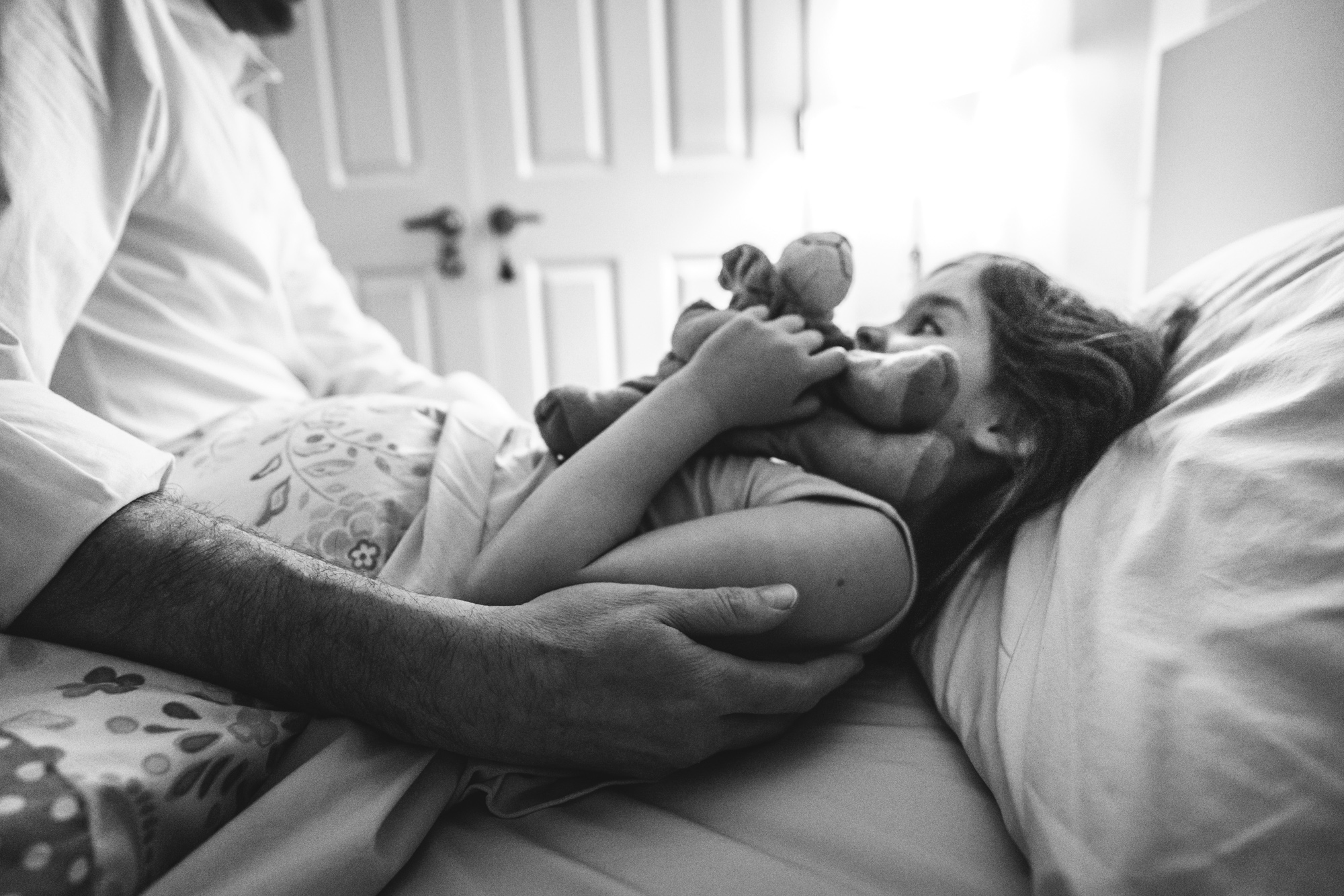 Black and white photo of a father tucking his young daughter into bed as she holds her stuffed lion close to her.