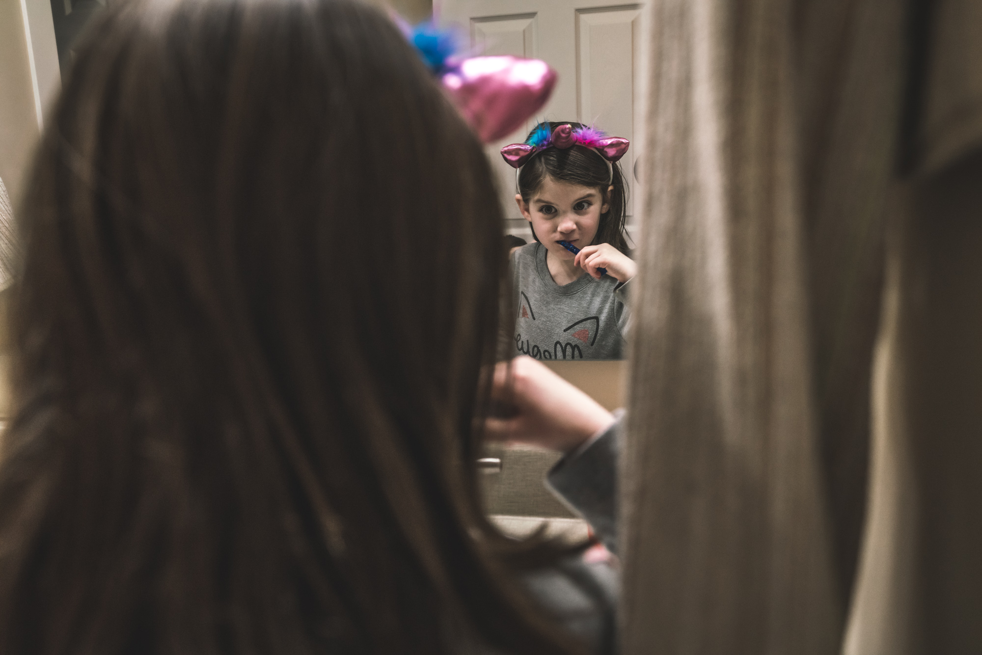Color photo of a little girl wearing a pink unicorn headband while brushing her teeth intently. Photo taken in her home in Denver, Colorado.