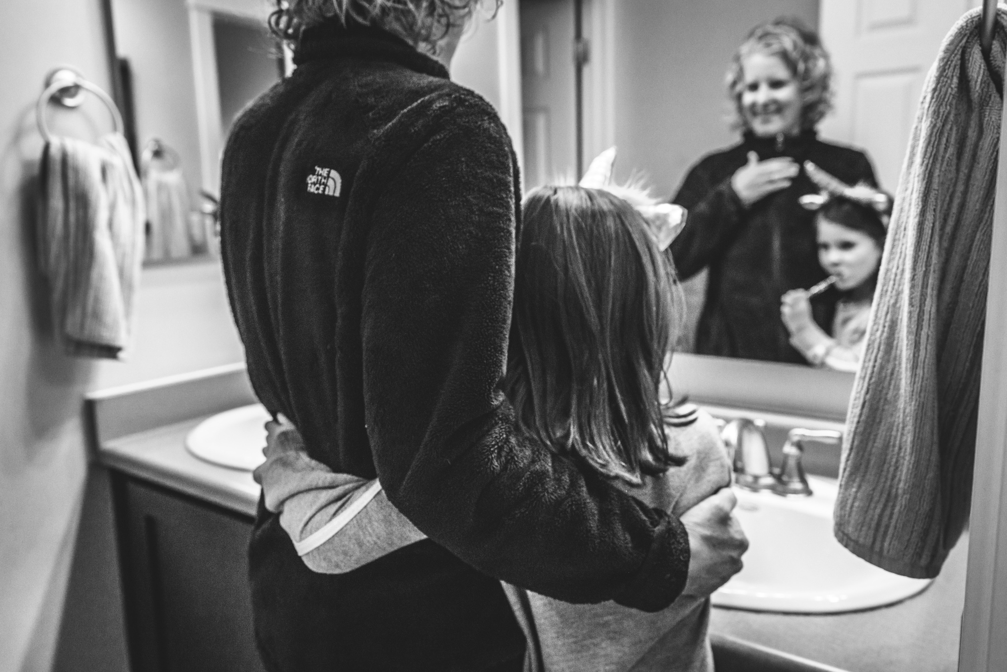 Black and white photo of a mother and daughter with their arms around each other as the little girl brushes her teeth. Photo taken at their home in Stapleton, Colorado.