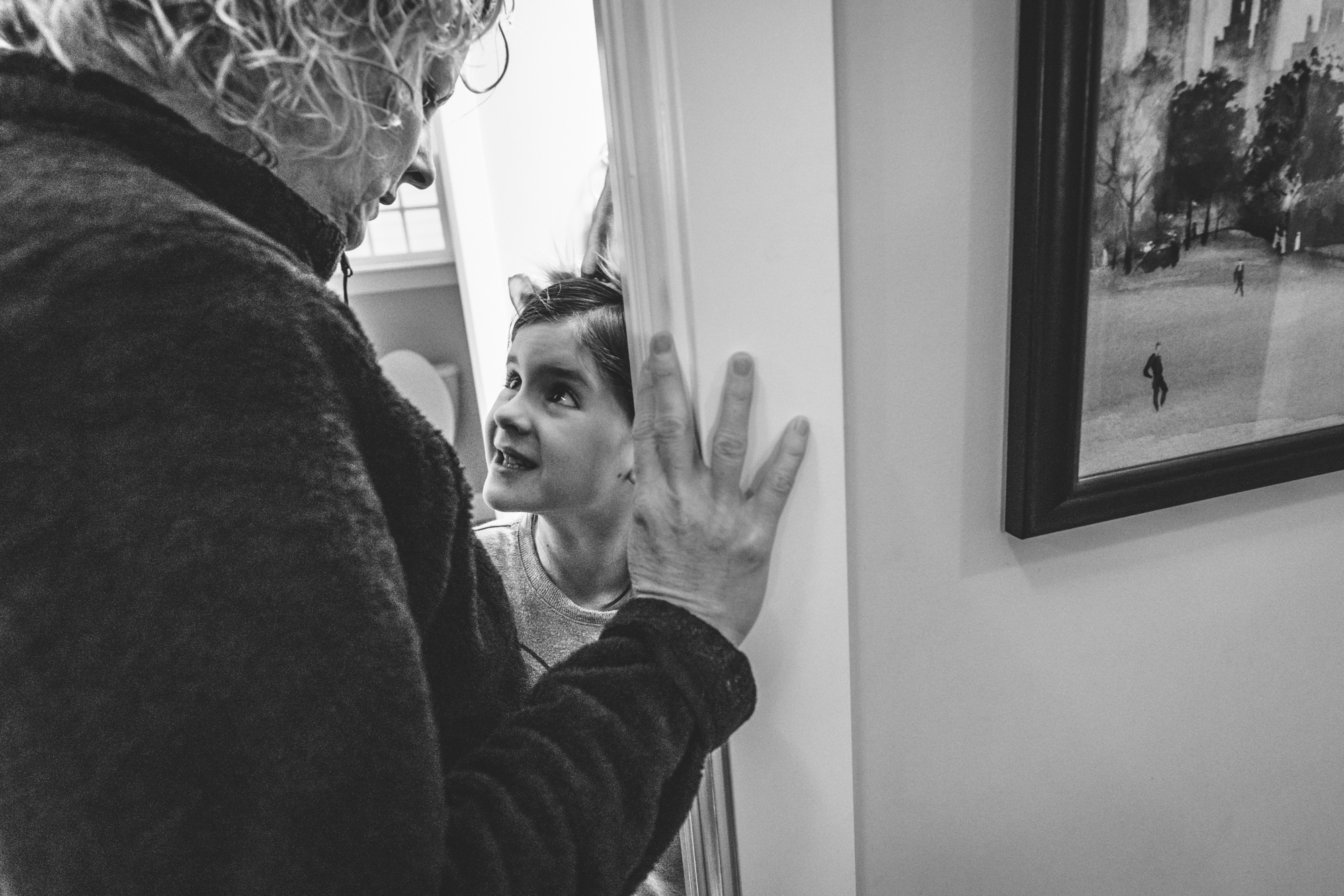 Black and white photo of a little girl looking up to her mommy in their bathroom at home in Denver, Colorado.