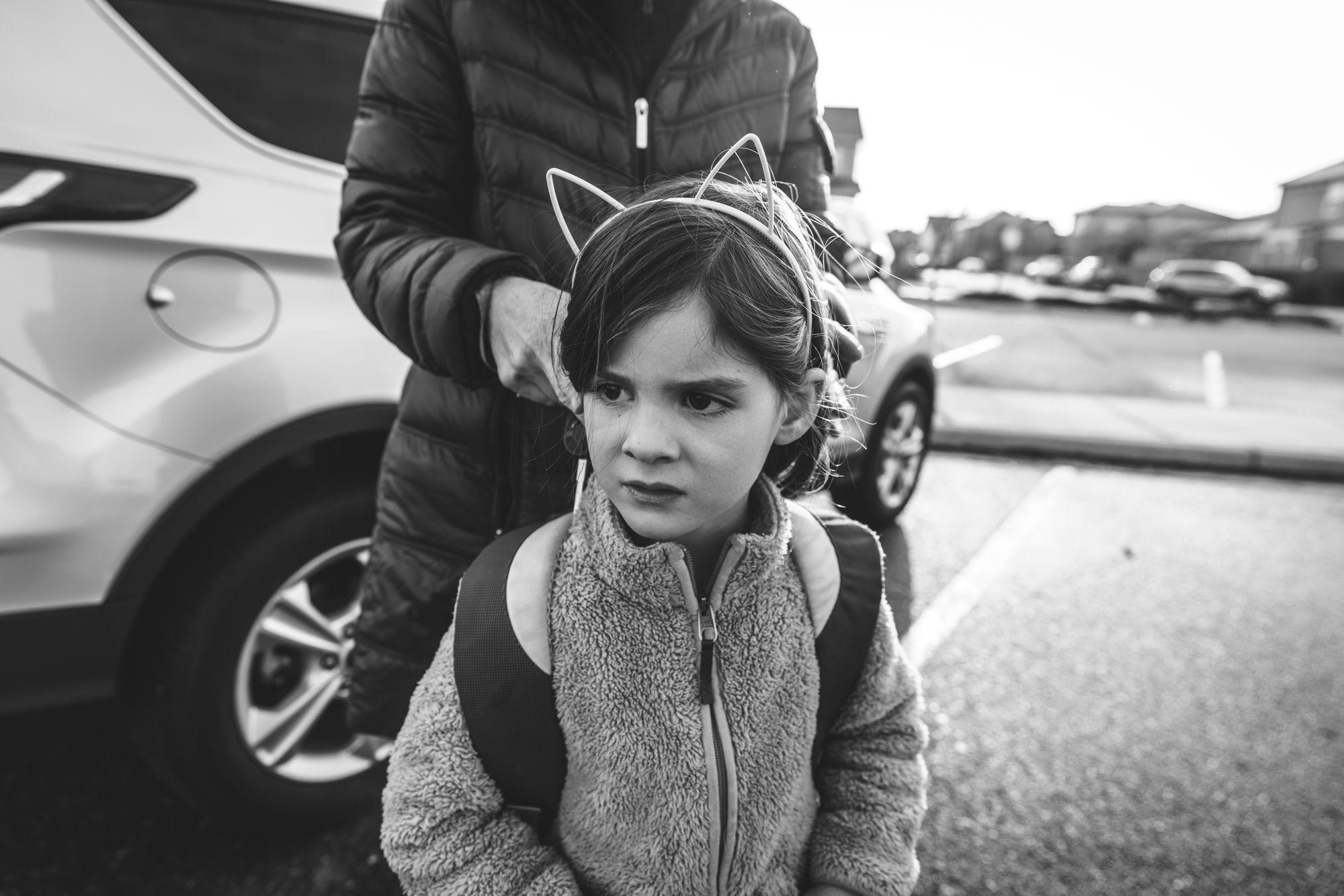 Black and white photo of a mother fixing her daughter's hair as the little girl wears a cat-ear headband outside of her school in Stapleton, Colorado