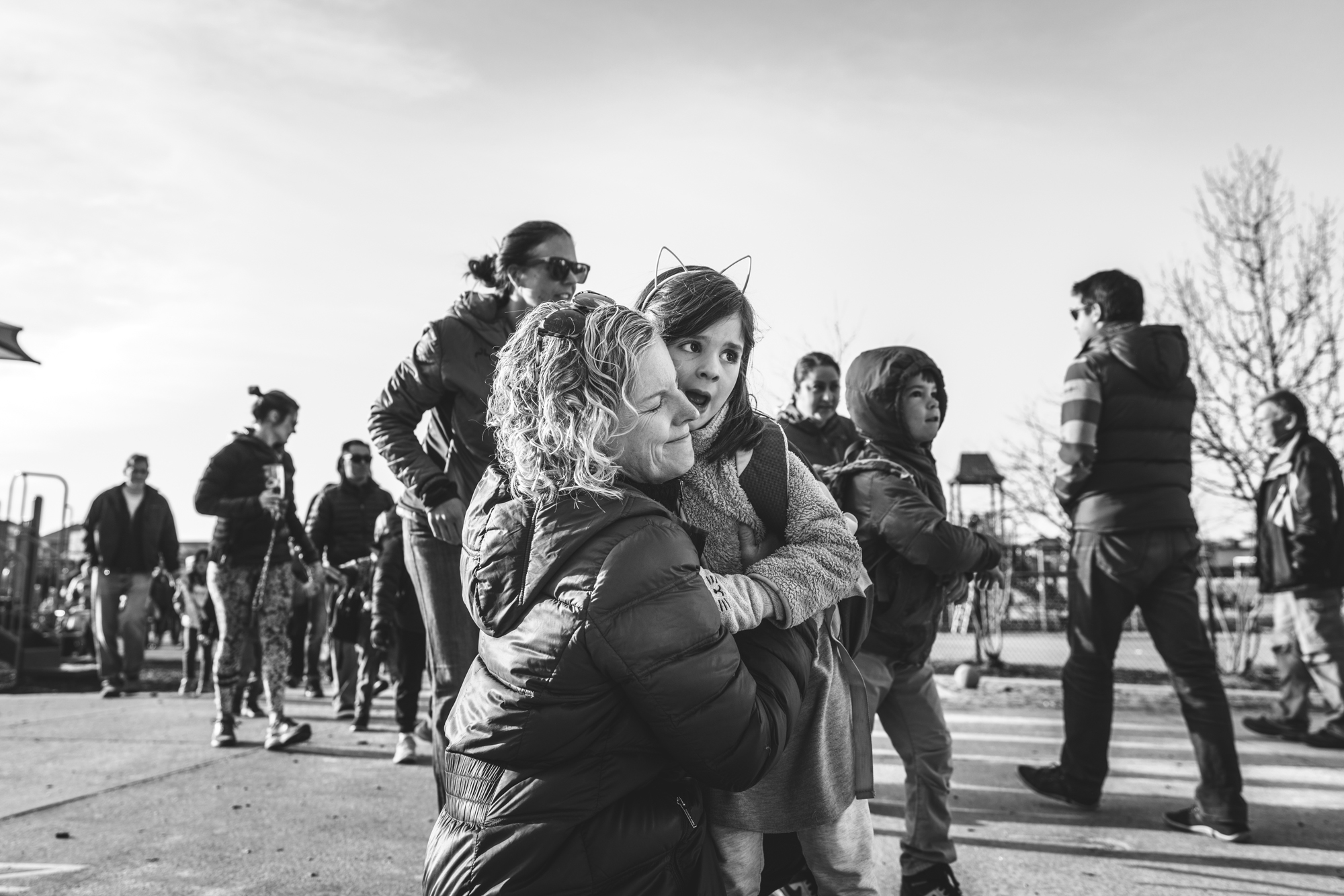 Black and white photograph of a mother and daughter outside of the little girls school in Denver, Colorado, hugging each other goodbye.