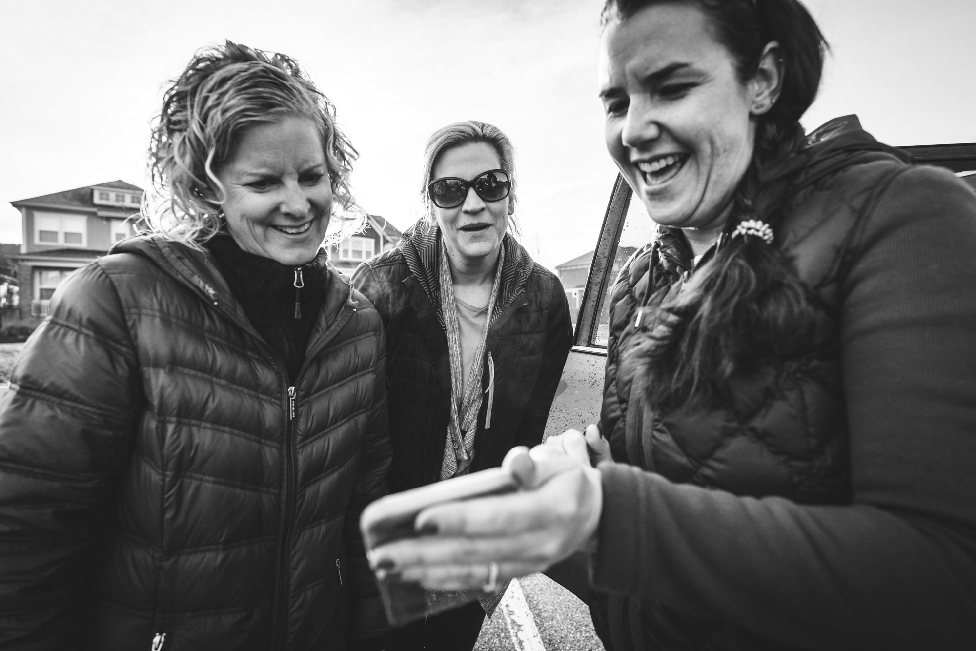 Black and white photo of three women standing in the parking lot of their children's school in Denver, Colorado, looking at something funny on a phone.