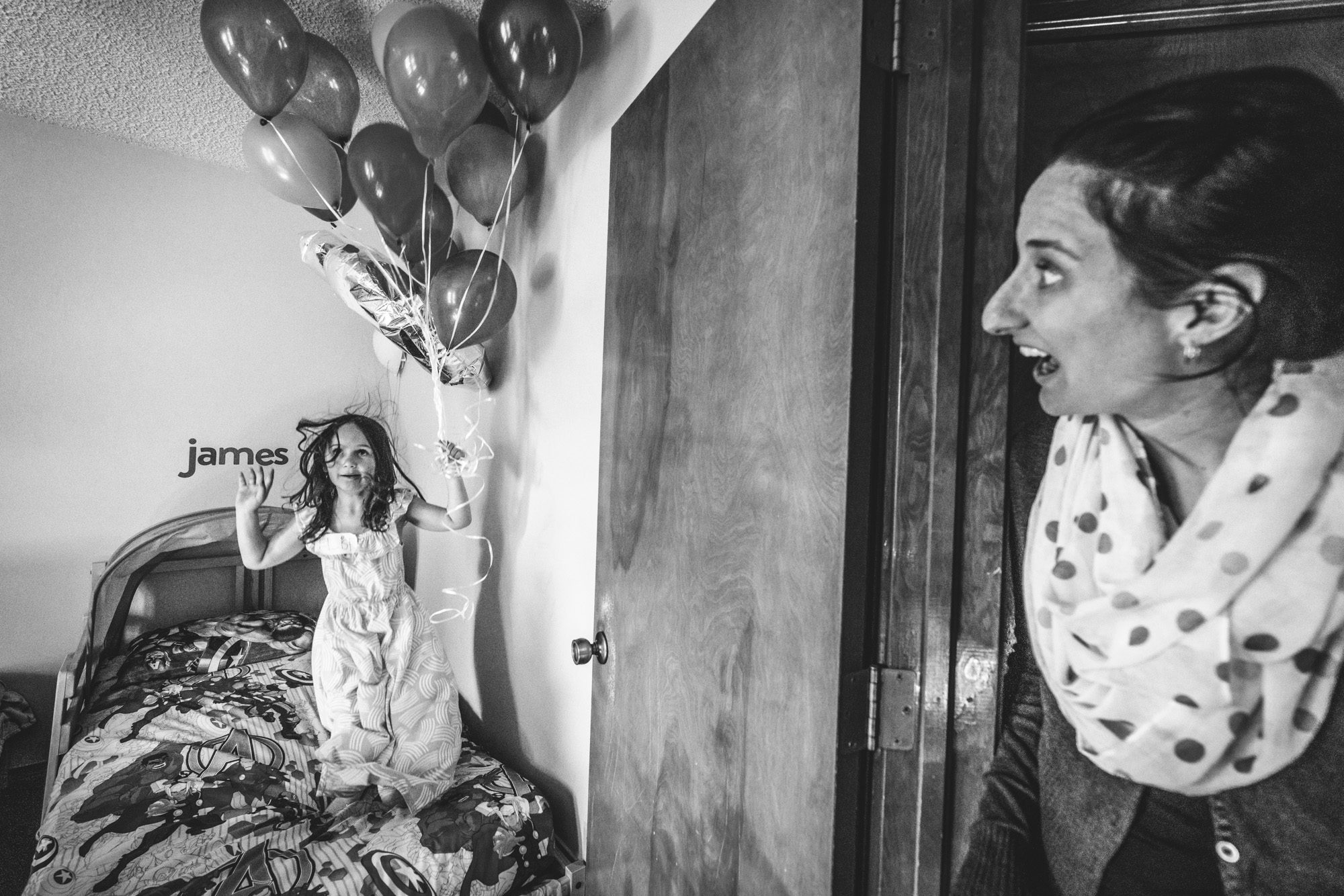 Black and white photo of a little girl at a birthday party, jumping on a bed while holding a bunch of balloons while her mother looks on with a shocked expression on her face, taken in Denver, Colorado