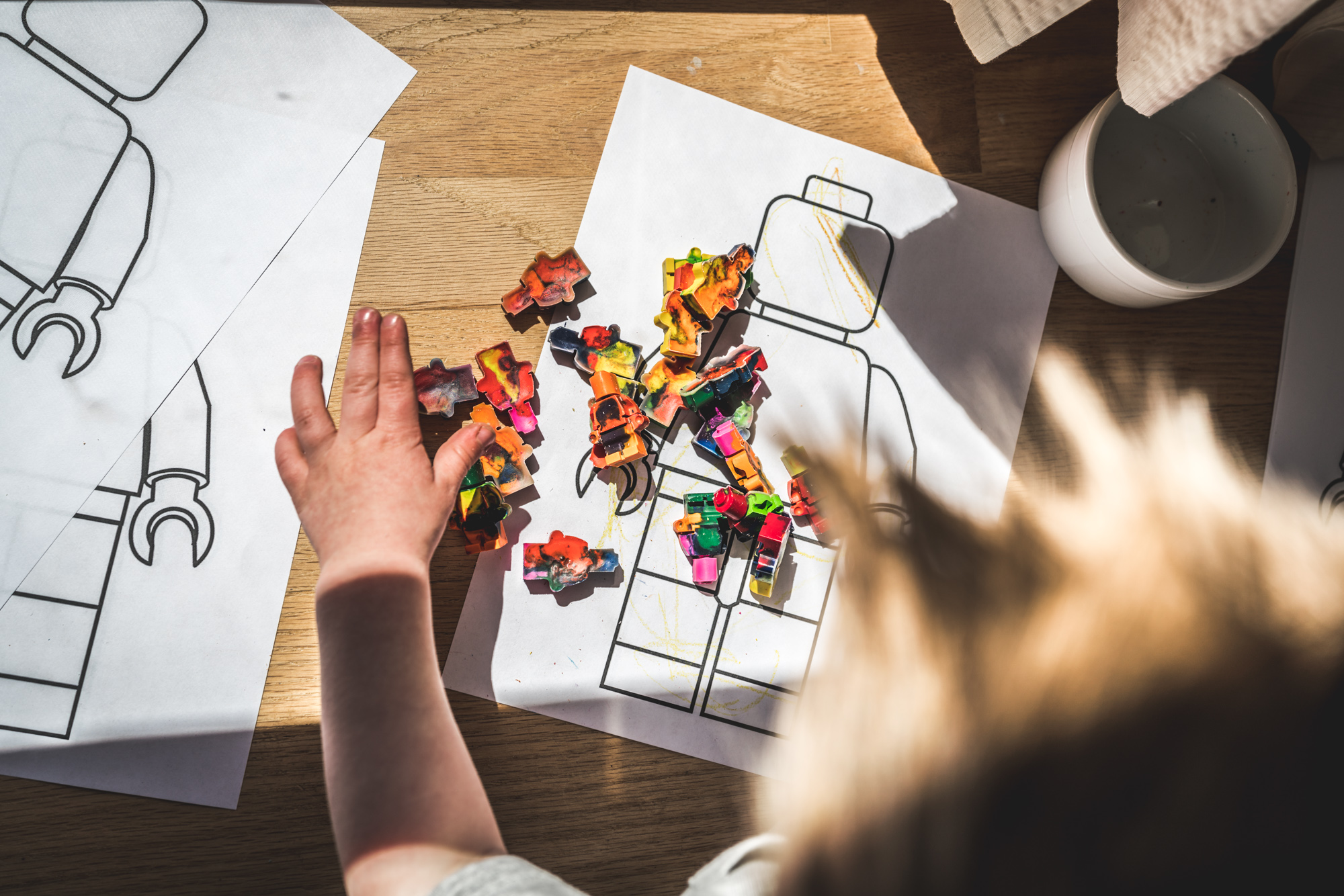 Color photo of a little boy playing with hand-made crayons shaped like lego men