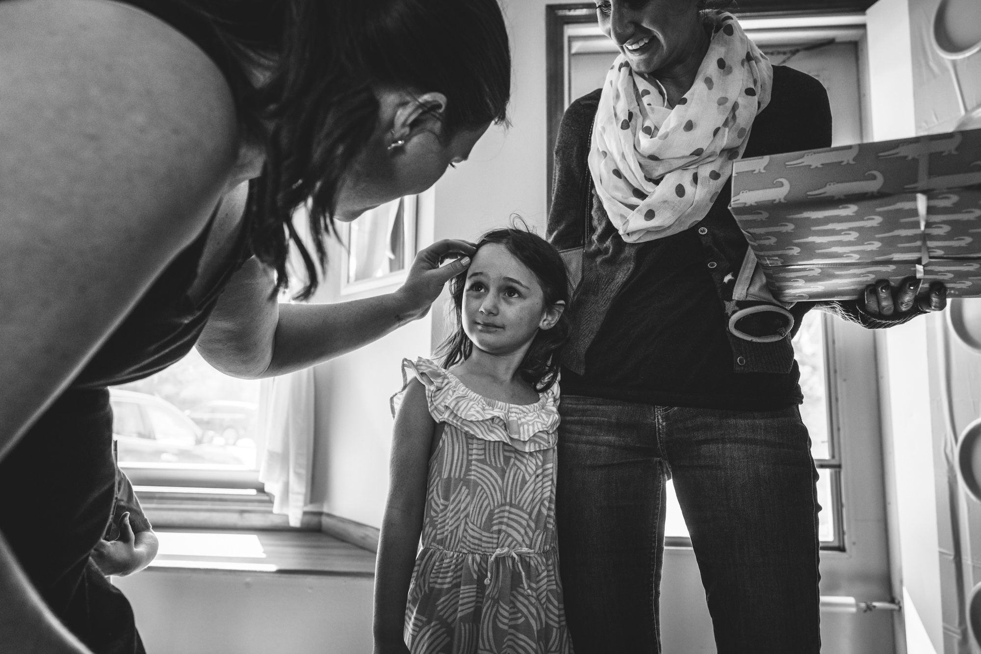 Black and white photo of a sweet little girl looking up at a woman as the woman softly pulls back the little girl's hair from her face