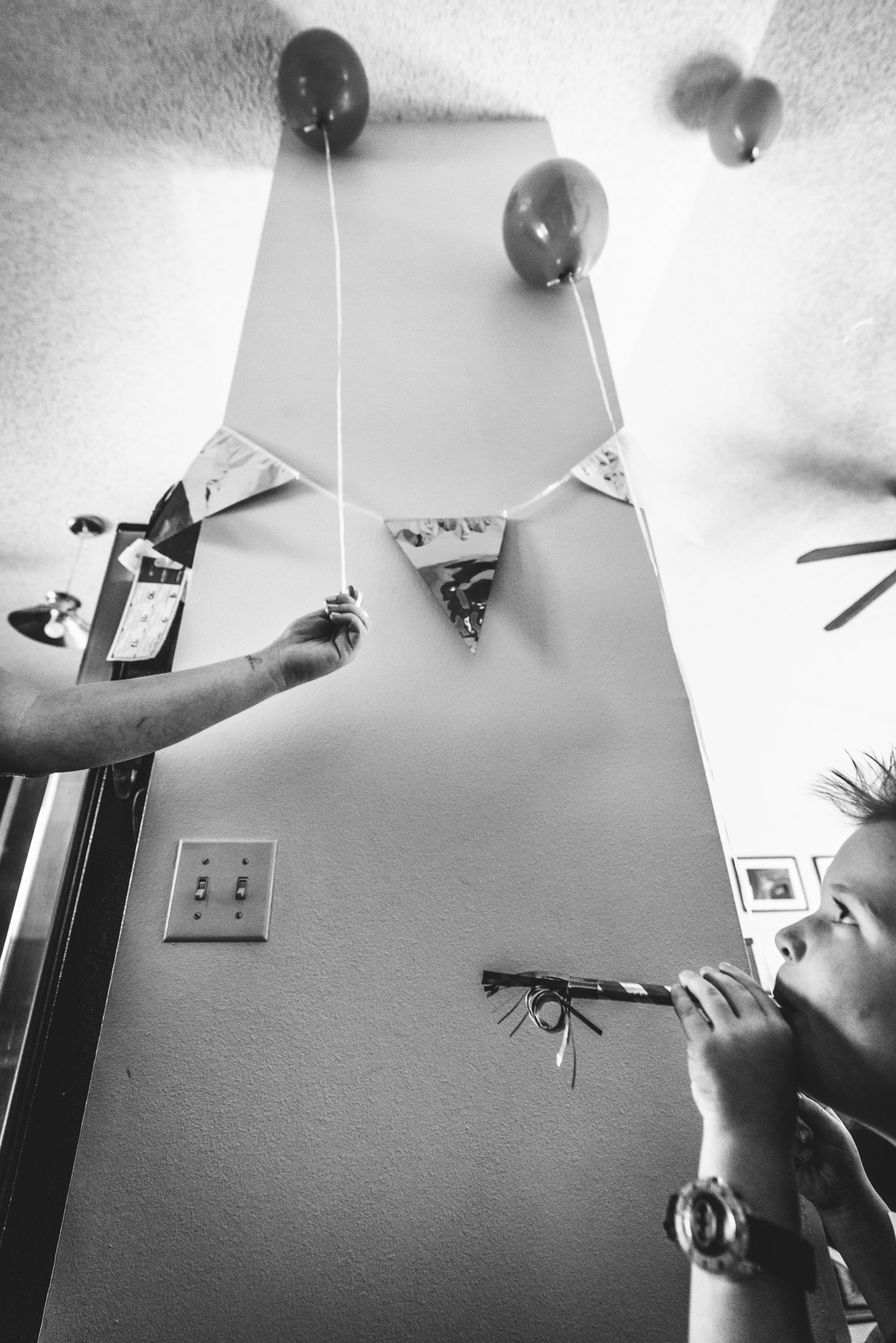 Black and white photo of a woman's arm retrieving a balloon for her son, who's blowing a party blower
